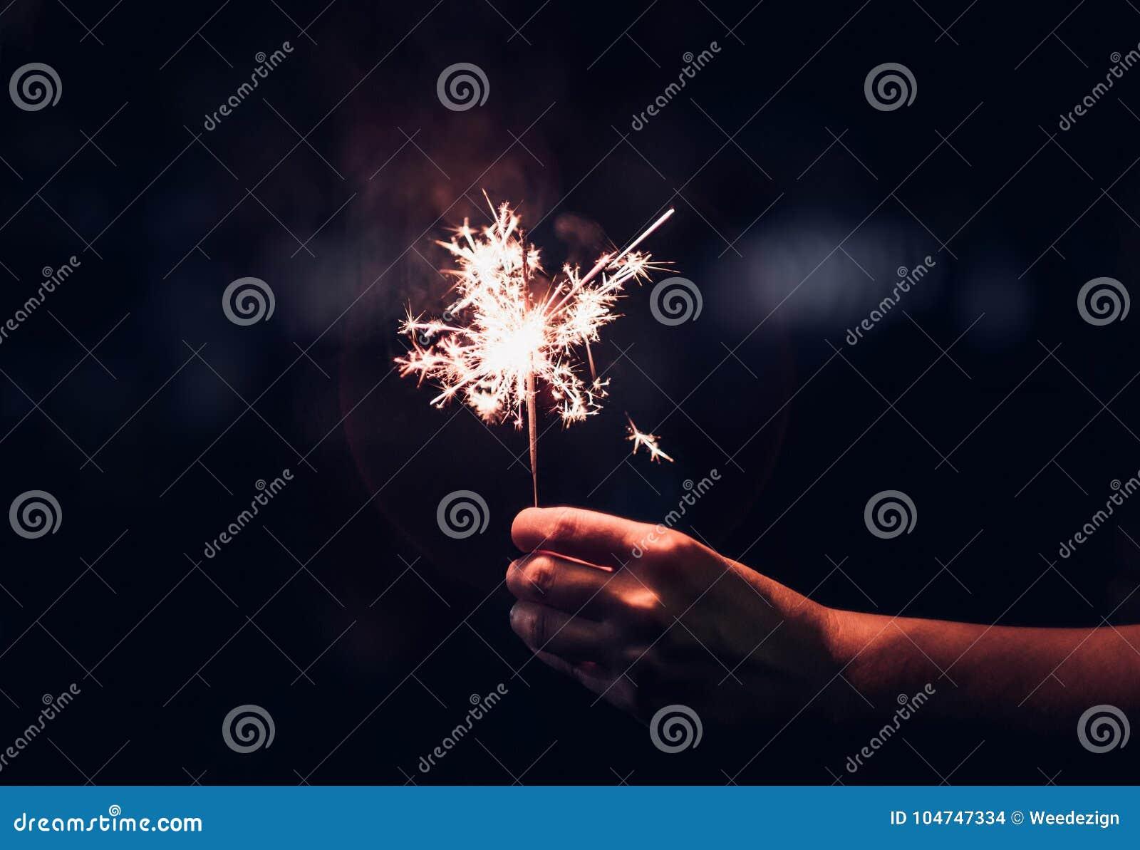 Übergeben Sie das Halten der brennenden Wunderkerzeexplosion auf einem schwarzen Hintergrund am nig
