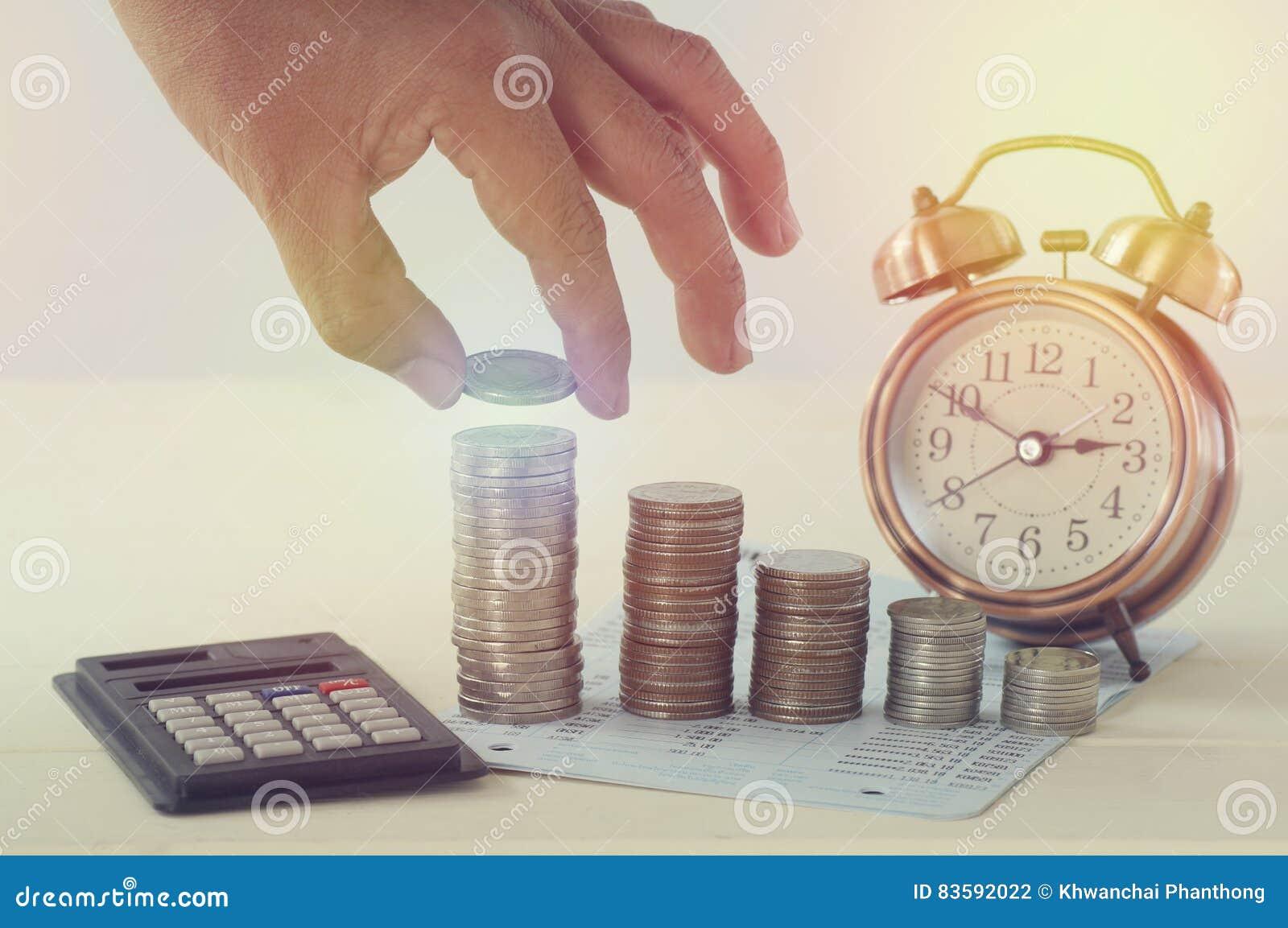 Übergeben Sie das Halten des Geldes auf Stapel von Münzen und von Weckerkonzept in der Abwehr