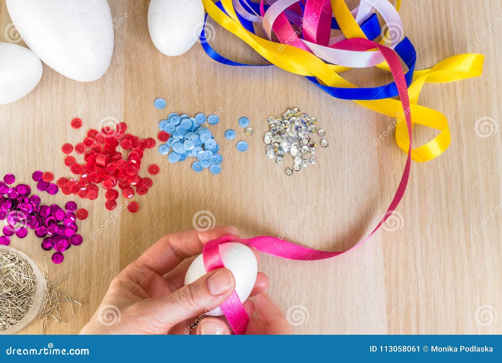 Übergeben Sie das Halten des Ostern-Polystyreneies, das rosa Band verziert