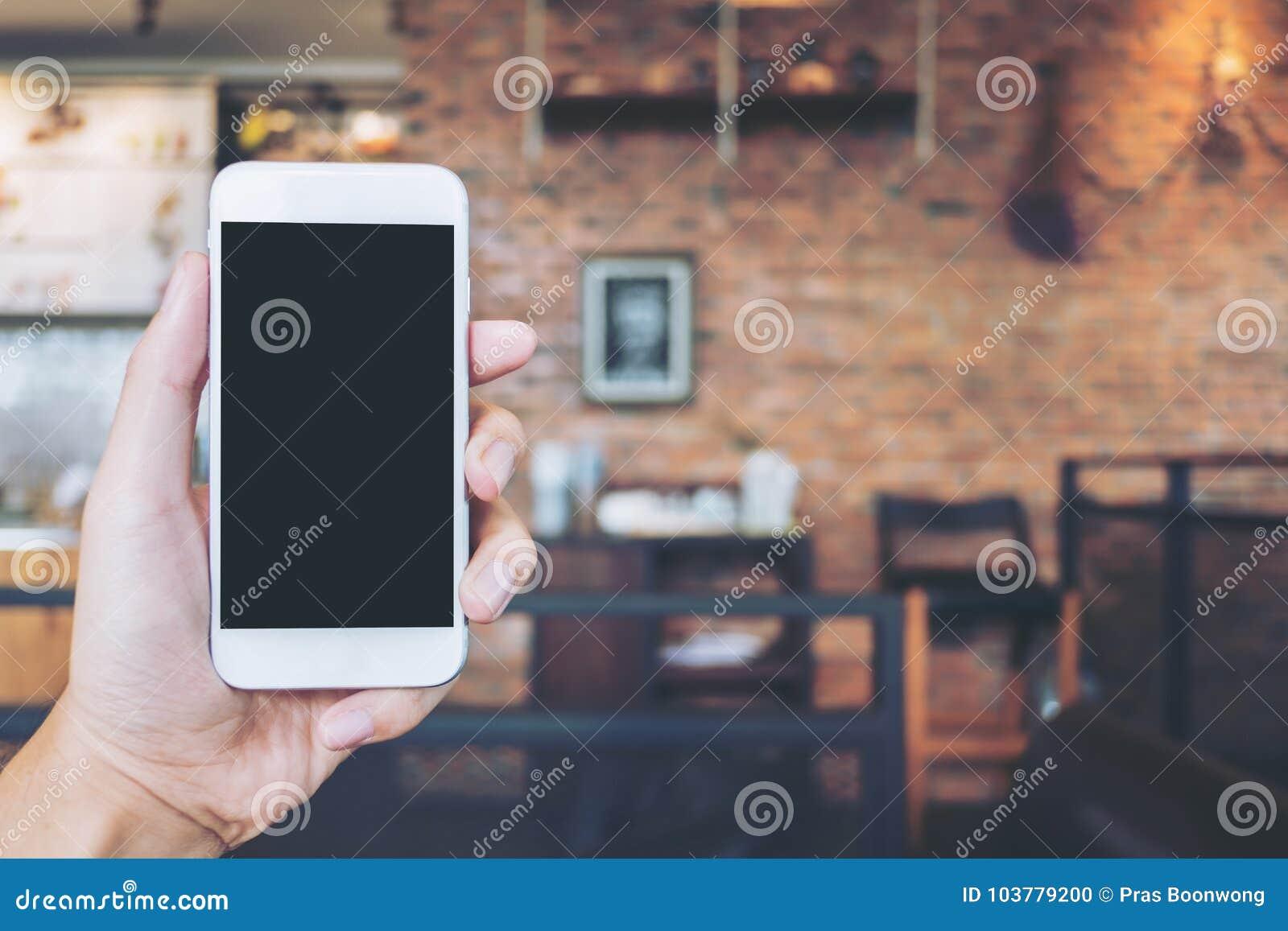 Übergeben Sie das Halten des weißen Handys mit leerem schwarzem Schirm im modernen Dachbodencafé