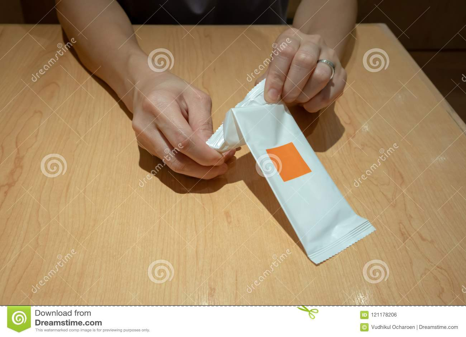 Übergeben Sie das Ziehen des nassen Papiers oder der Serviette von der Plastikverpackung