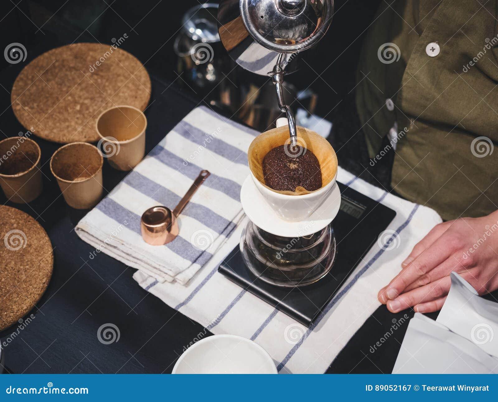 Übergeben Sie strömendes Wasser Tropfenfänger-Kaffee Barista auf Kaffeesatz mit fil