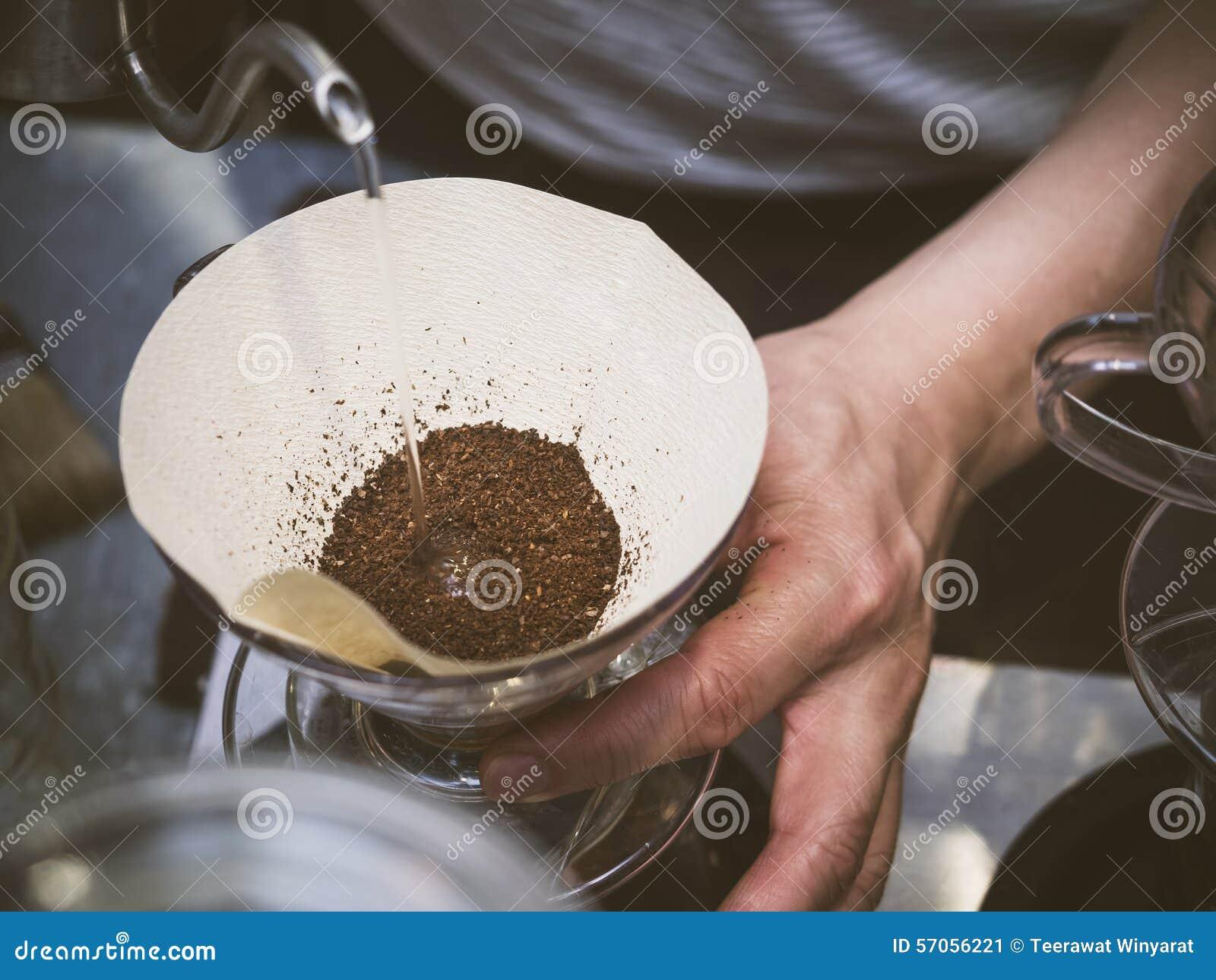 Übergeben Sie strömendes Wasser Tropfenfängerkaffee Barista auf Kaffeesatz