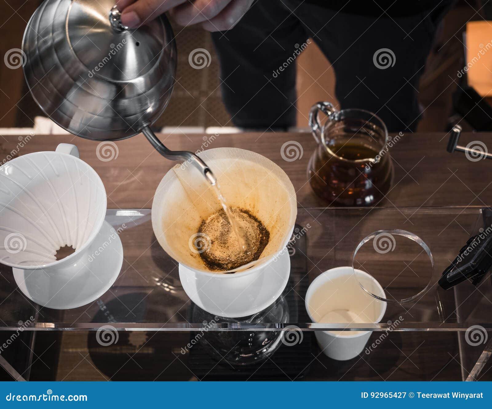 Übergeben Sie strömendes Wasser Tropfenfängerkaffee Barista auf Kaffeesatz mit Filter