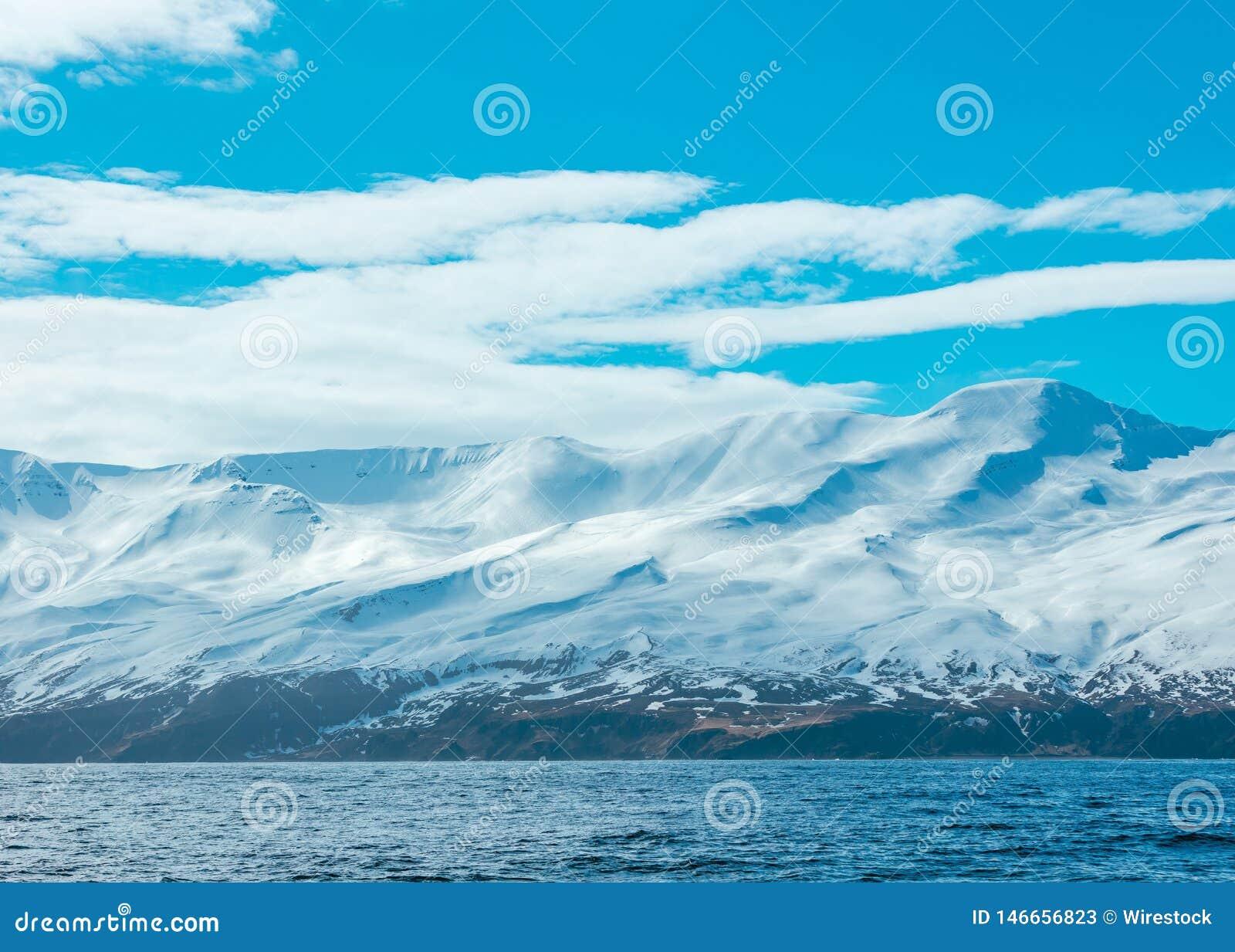 Überraschender Schuss von schneebedeckten Bergen und von Meer