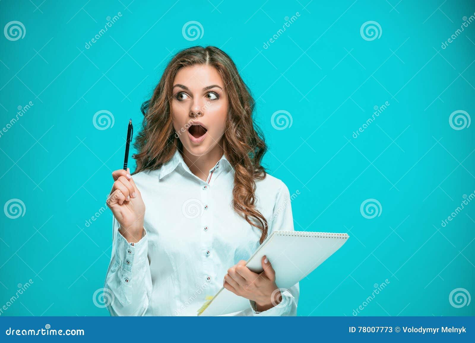 Überraschte junge Geschäftsfrau mit Tablette für Anmerkungen über blauen Hintergrund