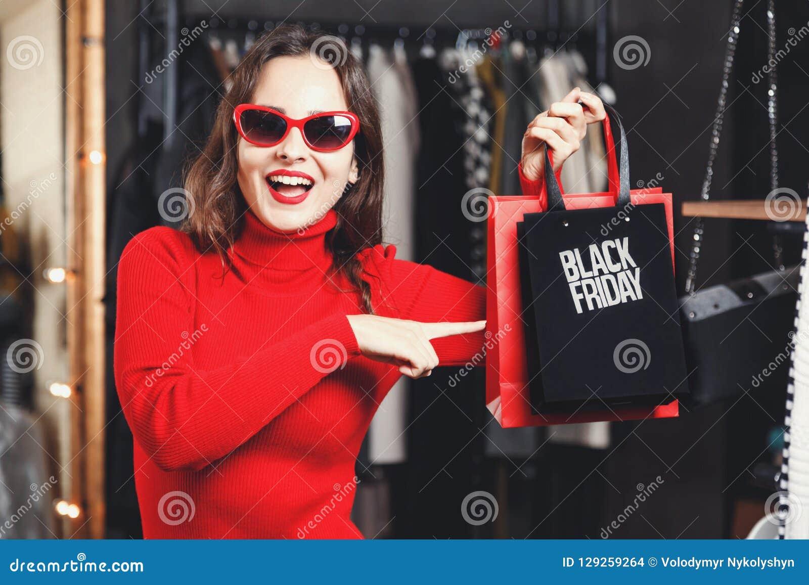 Überraschtes Mädchen, das Black Friday-Tasche zeigt