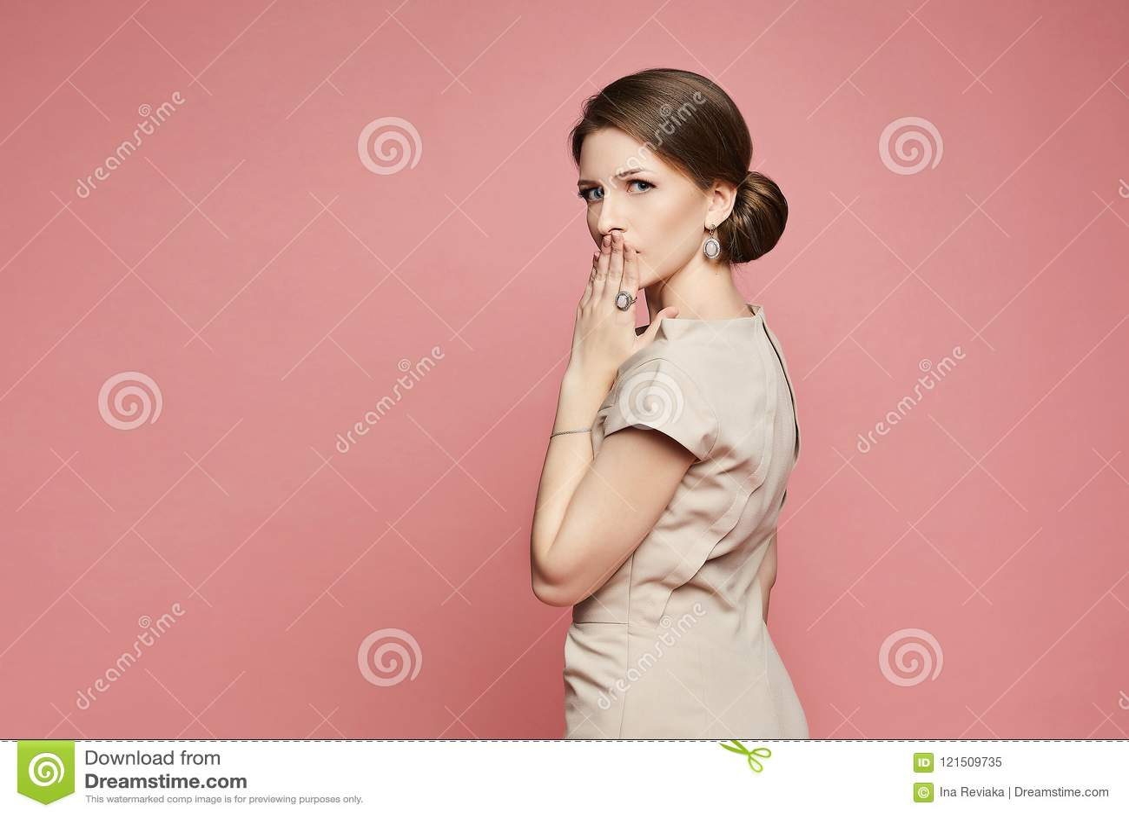 Überraschtes schönes und modernes Brunettemodellmädchen im beige Kleid und mit Ohrringen bedeckte ihren Mund mit ihrer Hand und p
