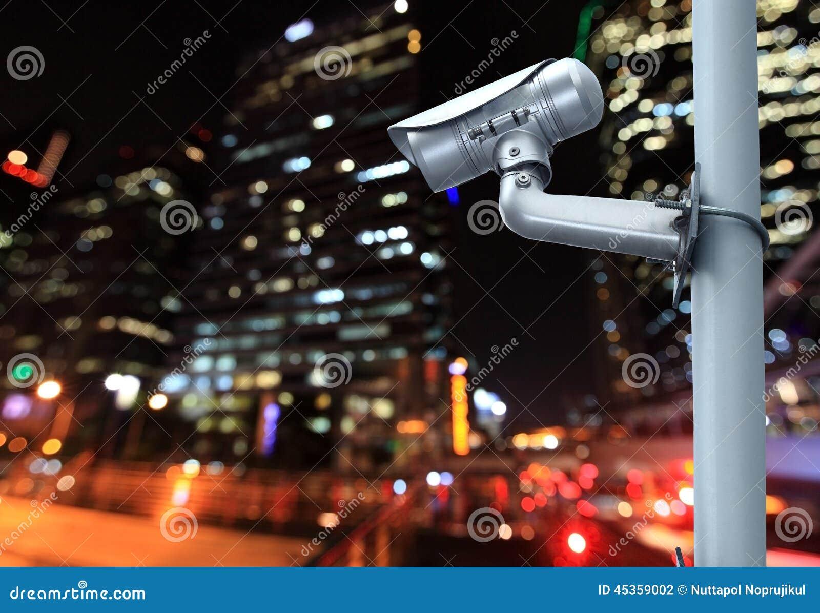 Überwachungskamera mit dem Verwischen der Nachtstadt im Hintergrund