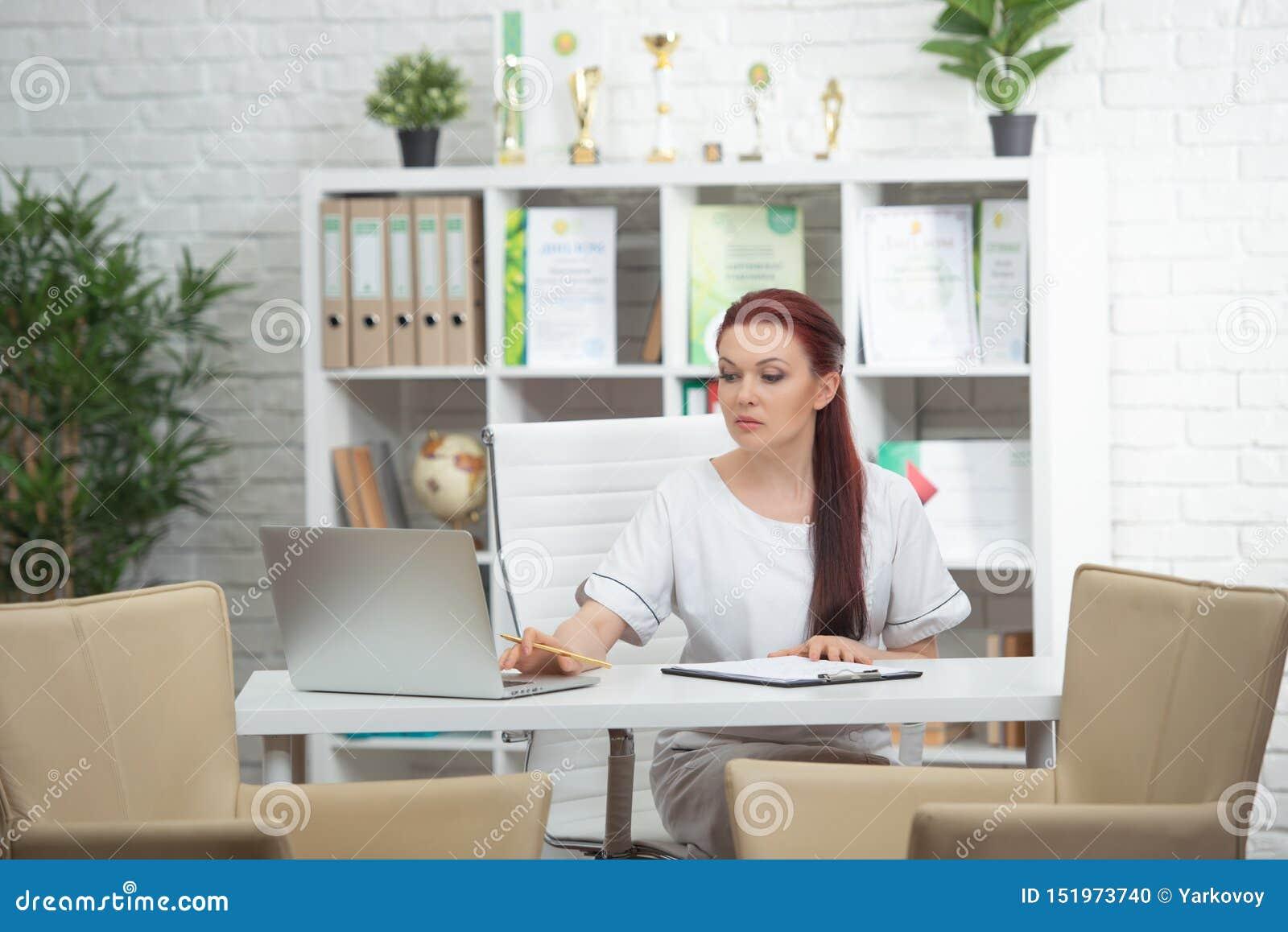 Überzeugte Ärztin, die am Tisch in ihrem Büro sitzt und an der Kamera lächelt Pille im hand