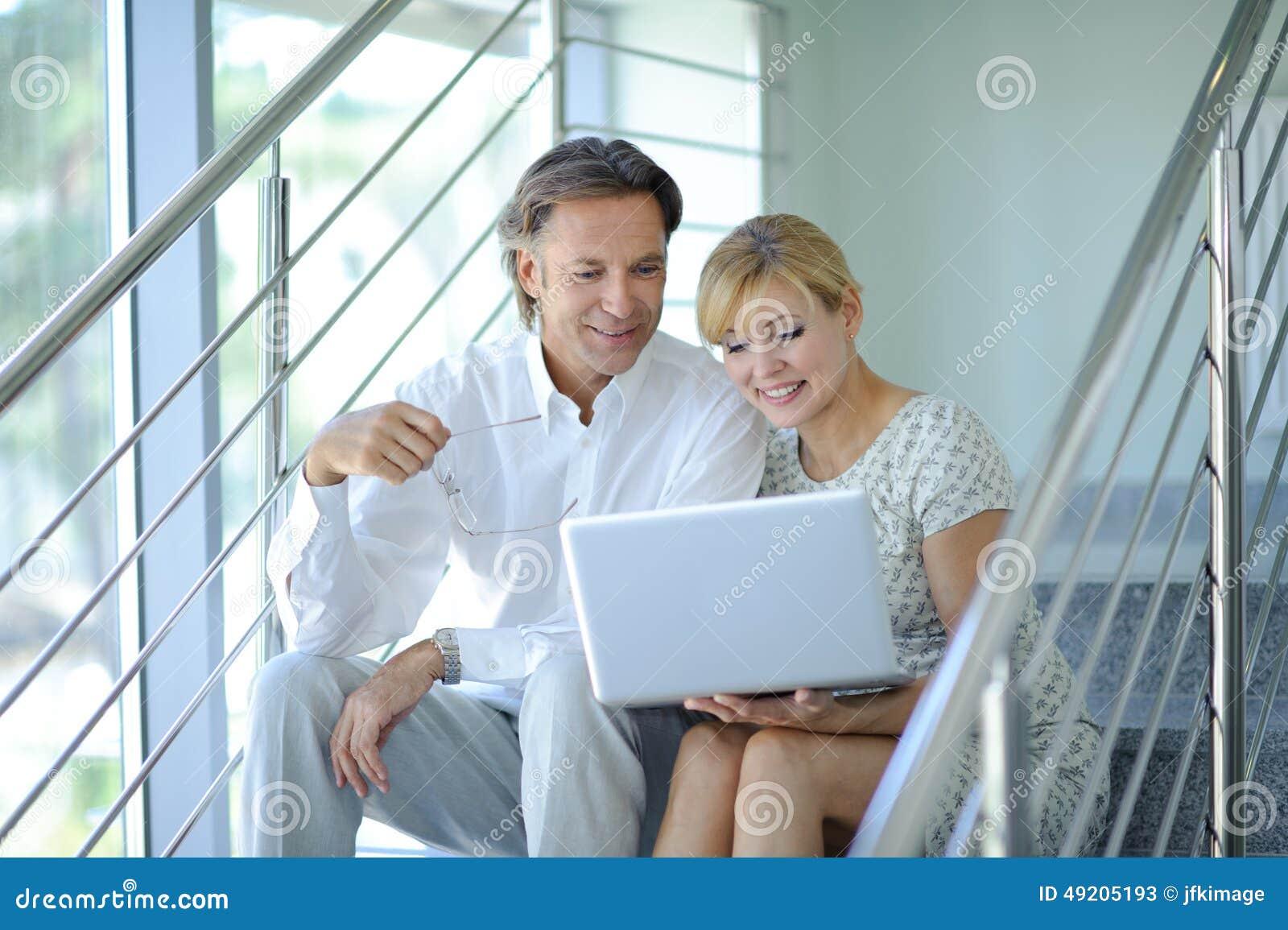 Überzeugte Teilhaber, die auf Treppe im Bürogebäude sitzen und Arbeit, Computer, lächelnd, reifer Geschäftsmann besprechen