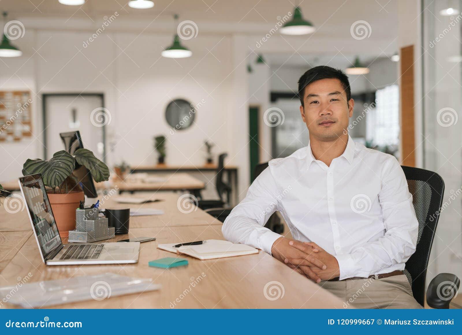 Überzeugter asiatischer Geschäftsmann, der an seinem Schreibtisch arbeitet