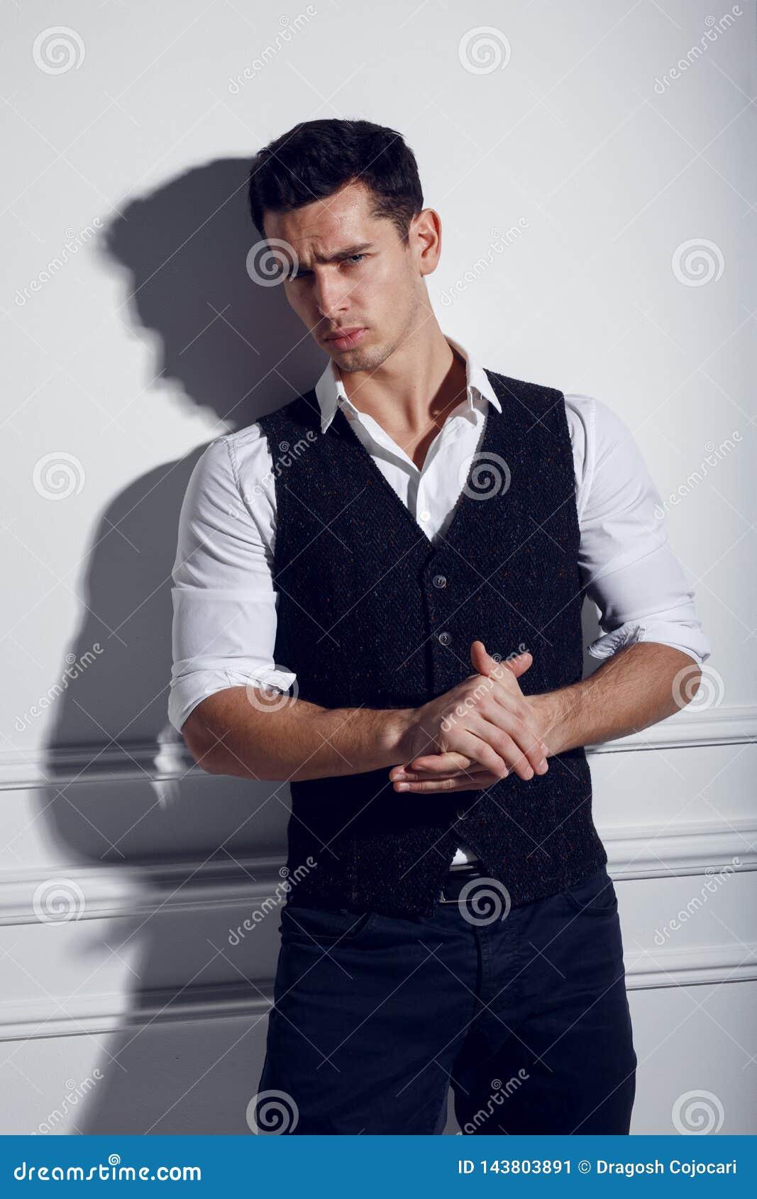 Überzeugter, attraktiver junger Mann in der eleganten Kleidung nahe der weißen Wand, werfend im Studio, Lichter des Studios auf