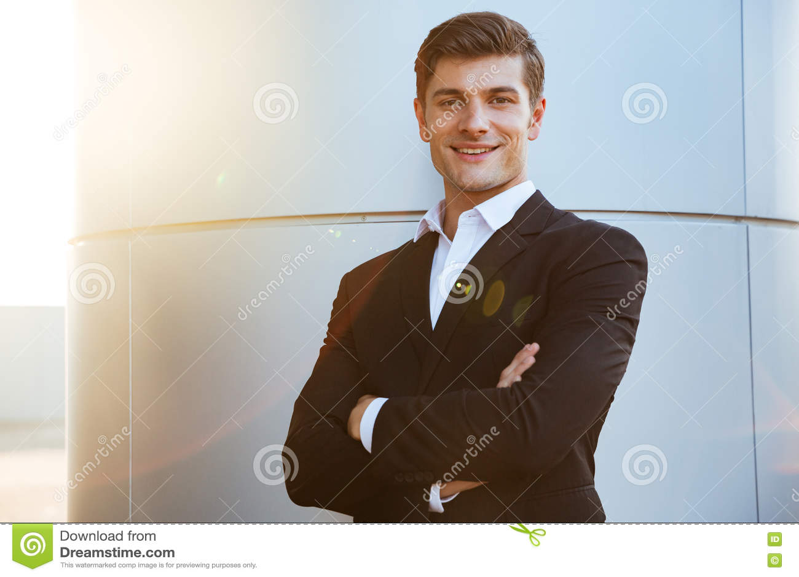 Überzeugter erfolgreicher junger Geschäftsmann, der mit den Armen gekreuzt steht
