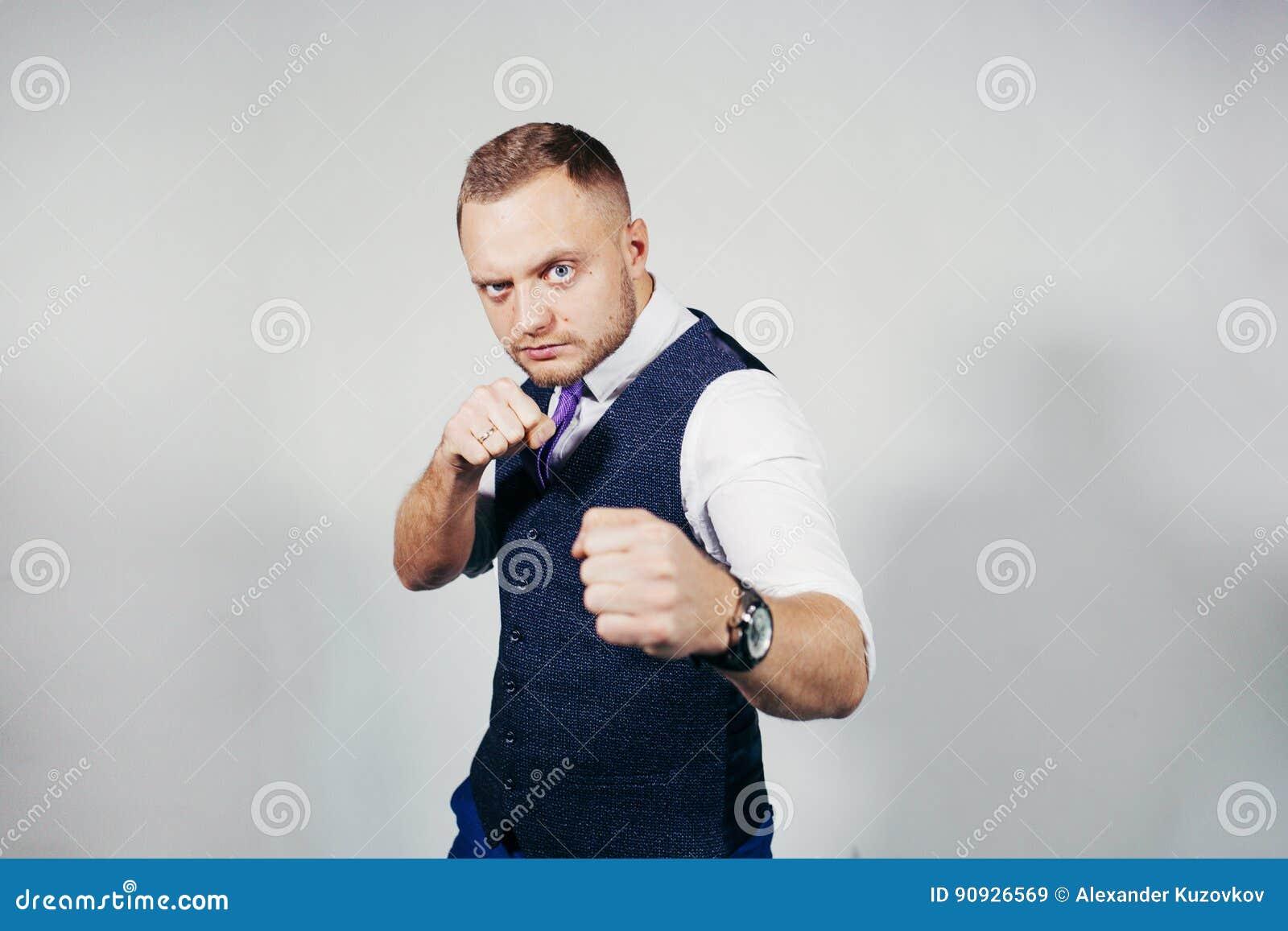 Überzeugter Geschäftsmann bereit zum Kampf über grauem Hintergrund Betrachten der Kamera