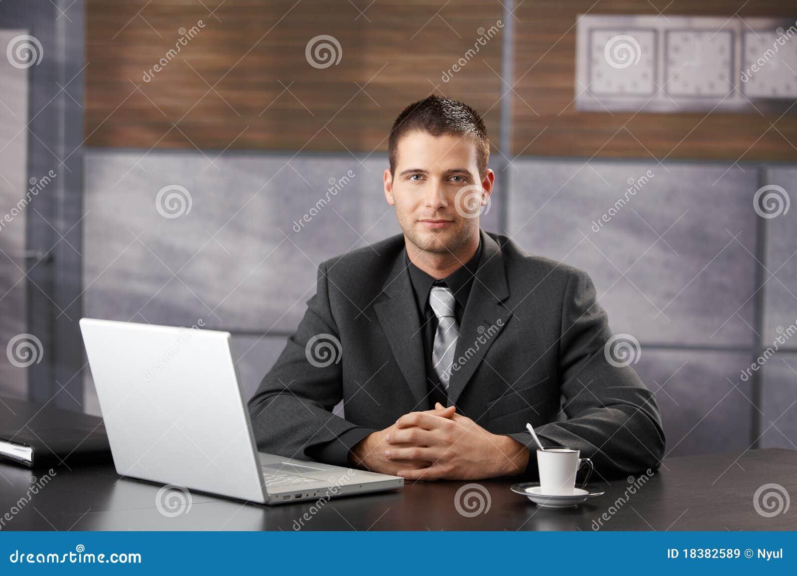 Überzeugter Manager, der im fantastischen Bürolächeln sitzt