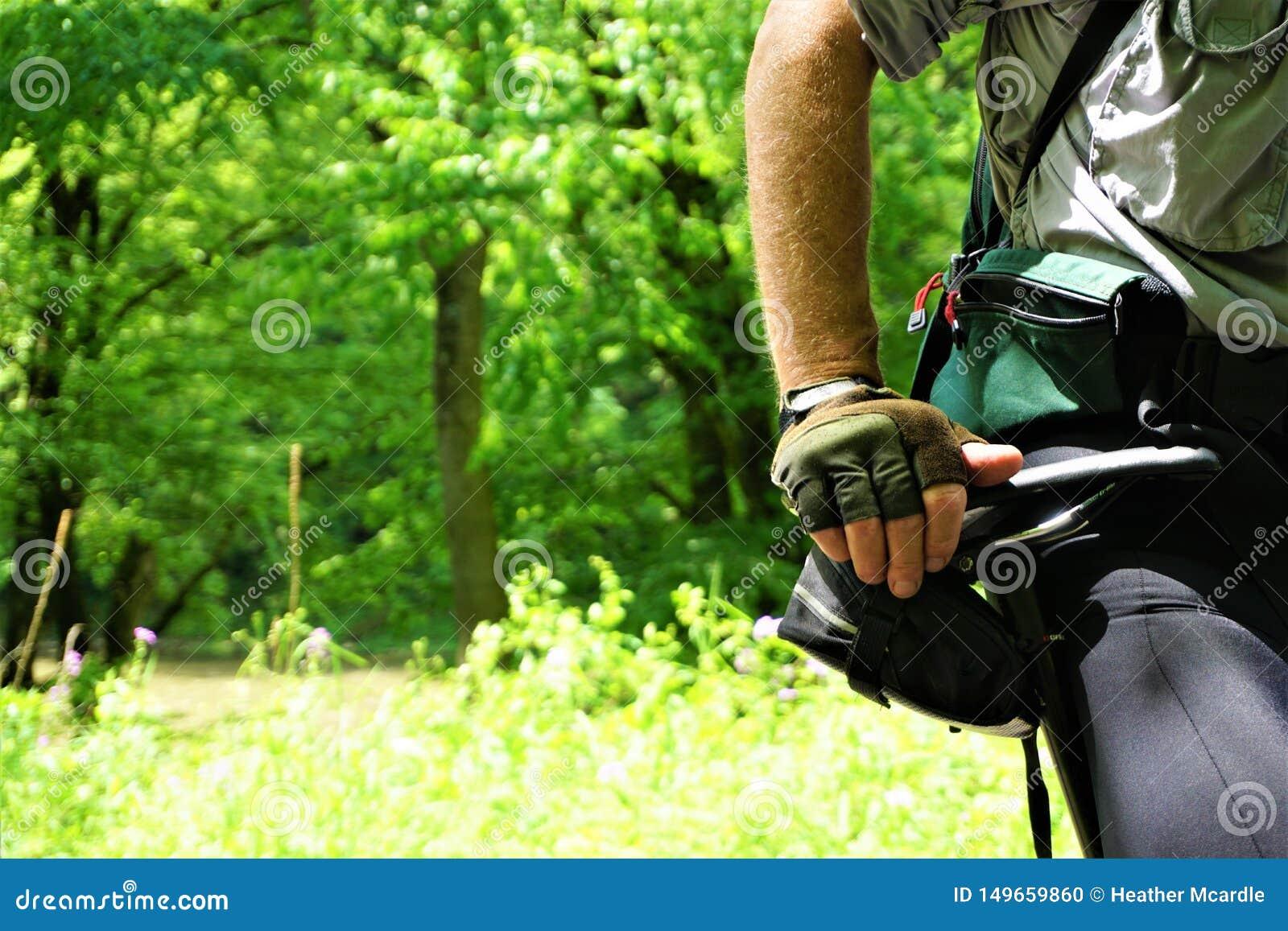 Überzeugter Mann auf stillstehender Hand des Fahrrades auf Hüfte