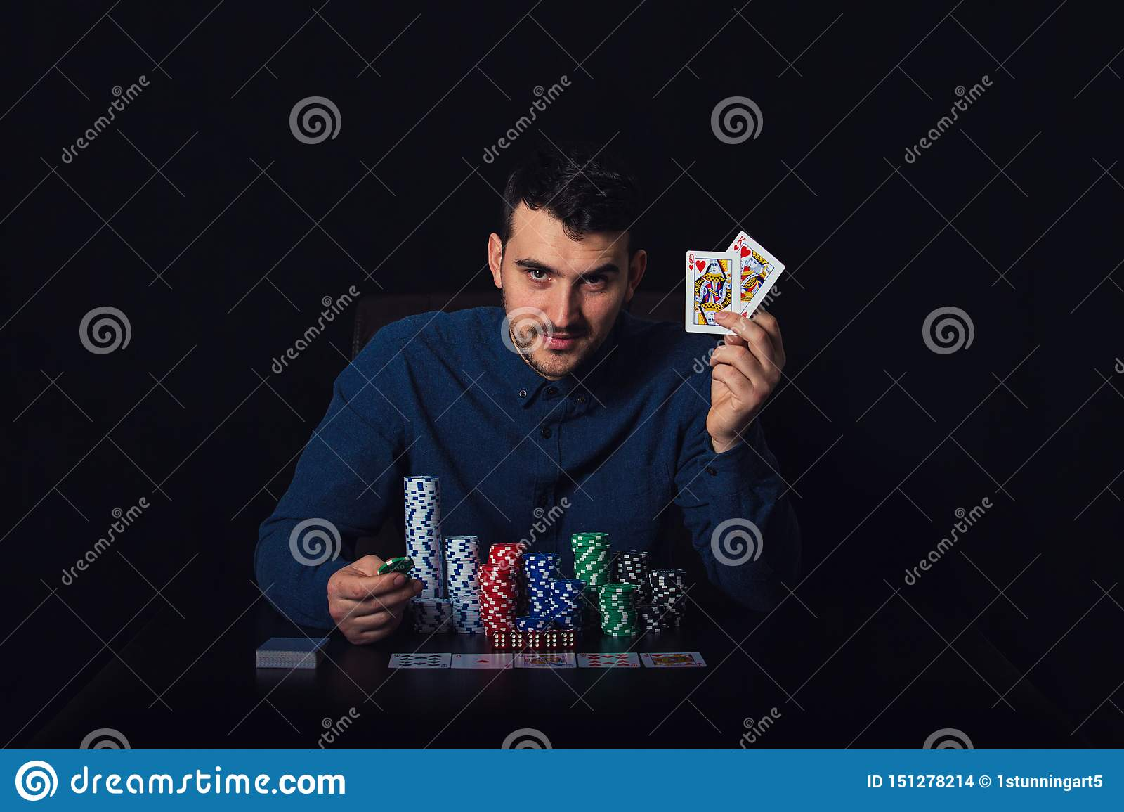Überzeugter Pokerspieler gesetzt am Kasinotisch, der seine gewinnenden Karten über schwarzem Hintergrund zeigt Spielender Turnier