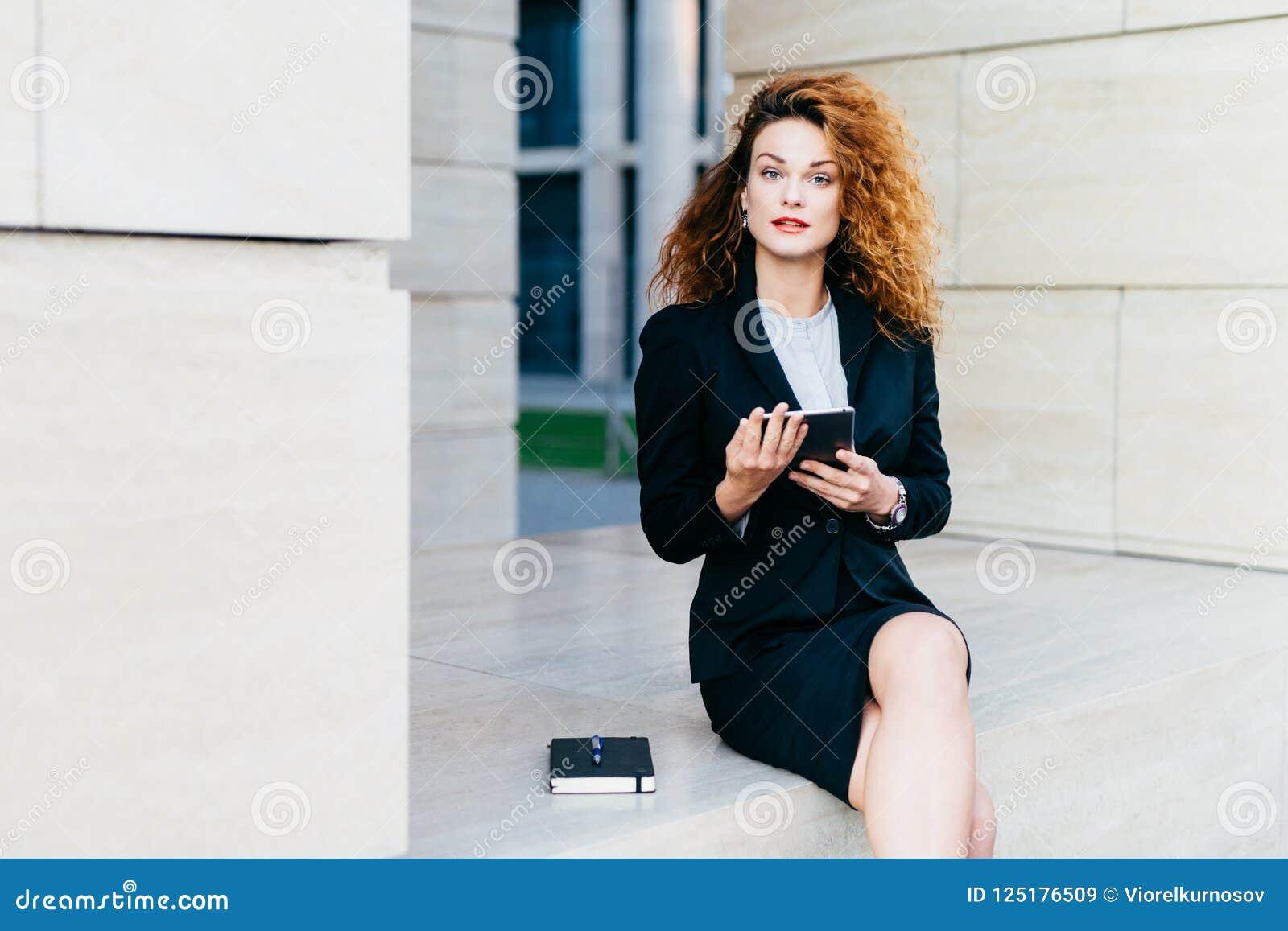 Überzeugter weiblicher Freiberufler, der beim Arbeiten mit ihrer Tablette, Anmerkungen in ihr Taschenbuch schreibend, tragendes s