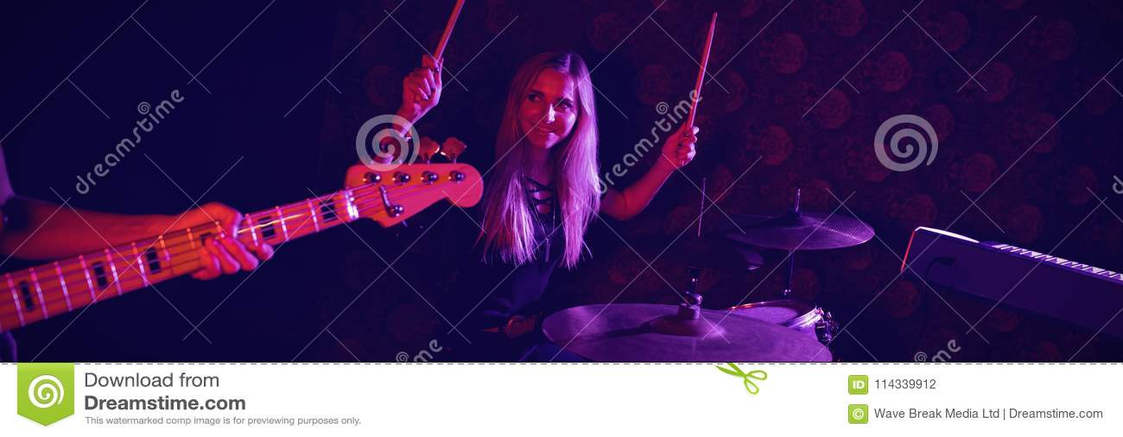Überzeugter weiblicher Schlagzeuger, der Gitarristen bei der Ausführung am Stadium betrachtet