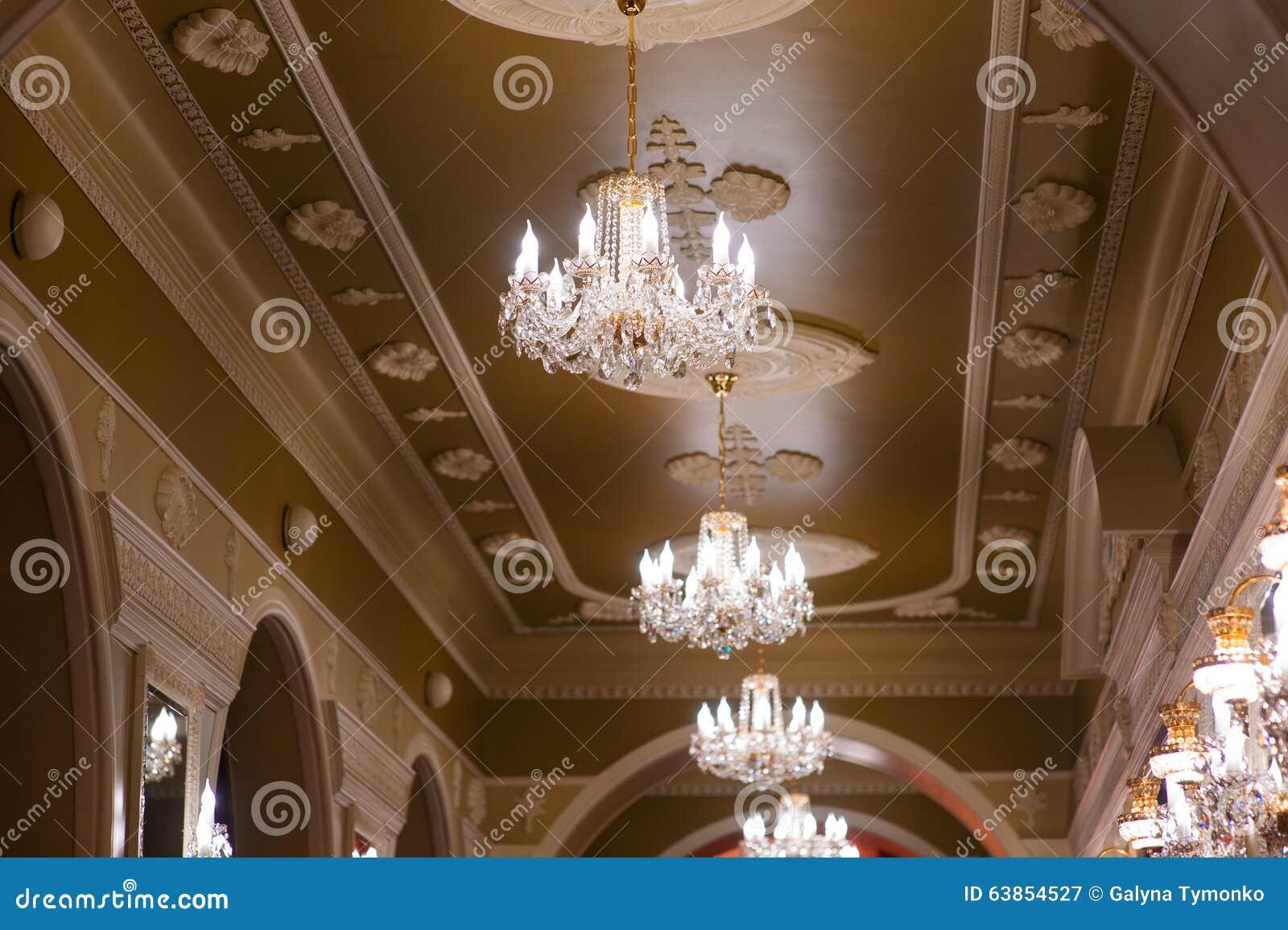 美丽的发光的枝形吊灯在宫殿的大厅里.图片