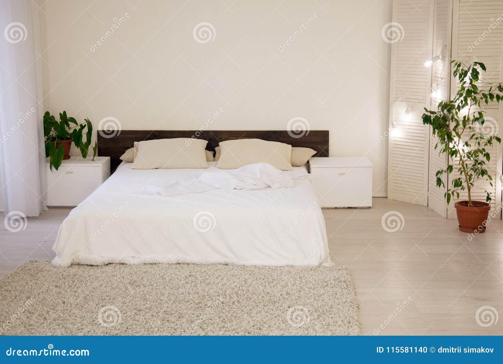 łóżkowe I Zielone Rośliny W Białej Sypialni Zdjęcie Stock