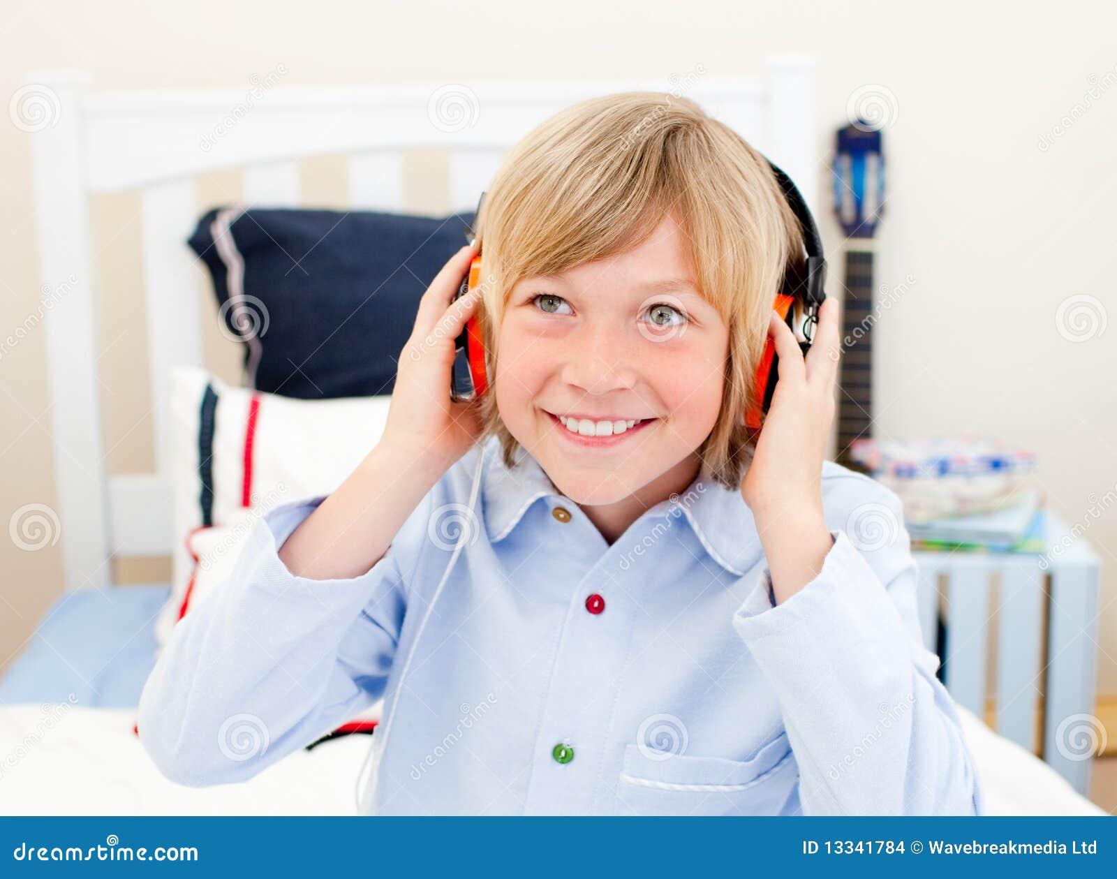 łóżkowej chłopiec szczęśliwy słuchający muzyczny obsiadanie