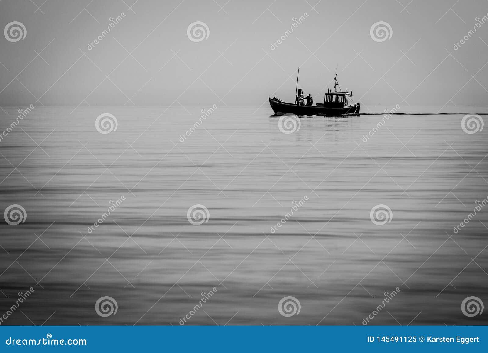 Łódź rybacka wychodzi morze wcześnie rano gdy morze jest spokojny
