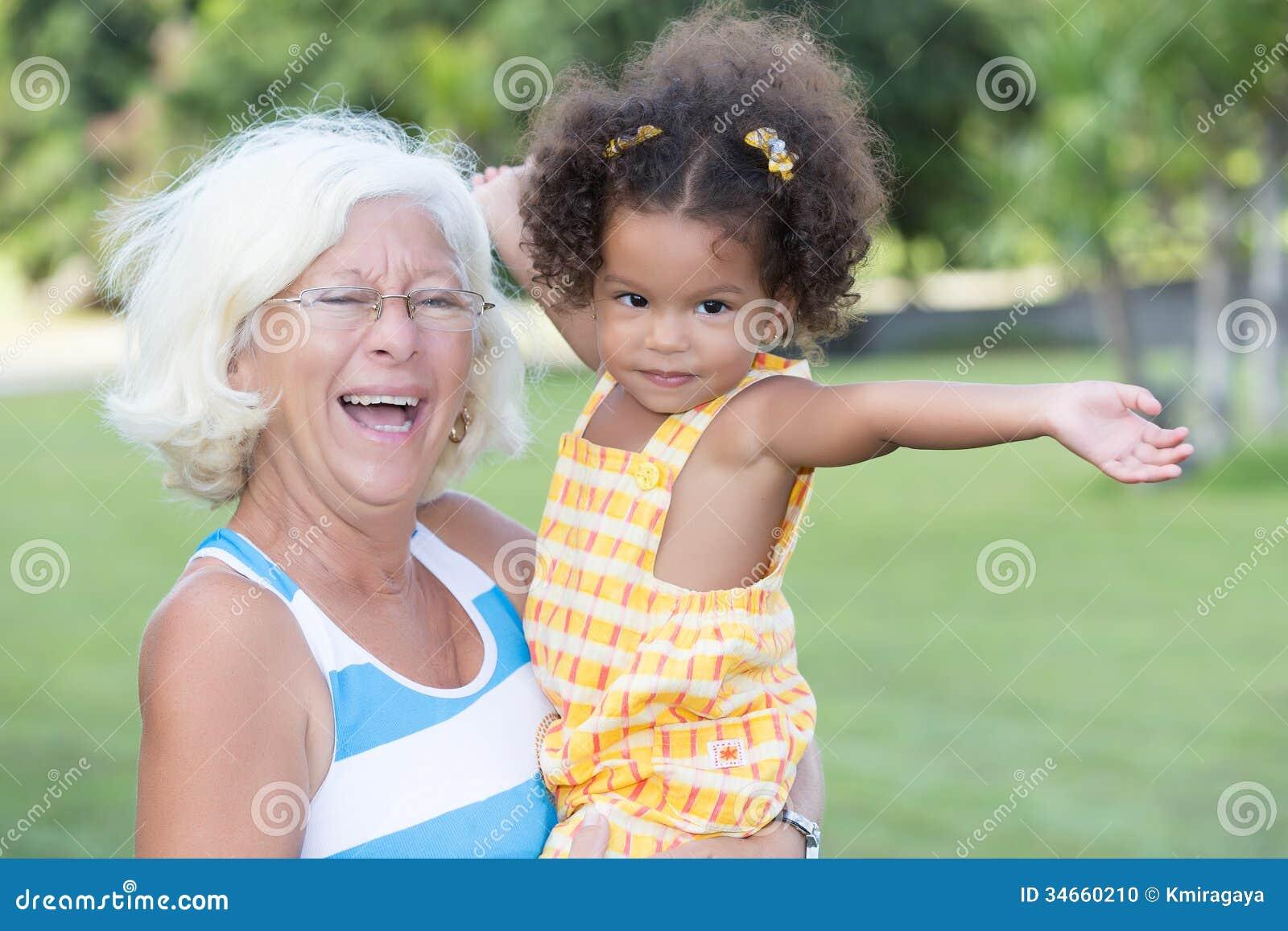 Łacińska dziewczyna i jej caucasian babci przytulenie w parku