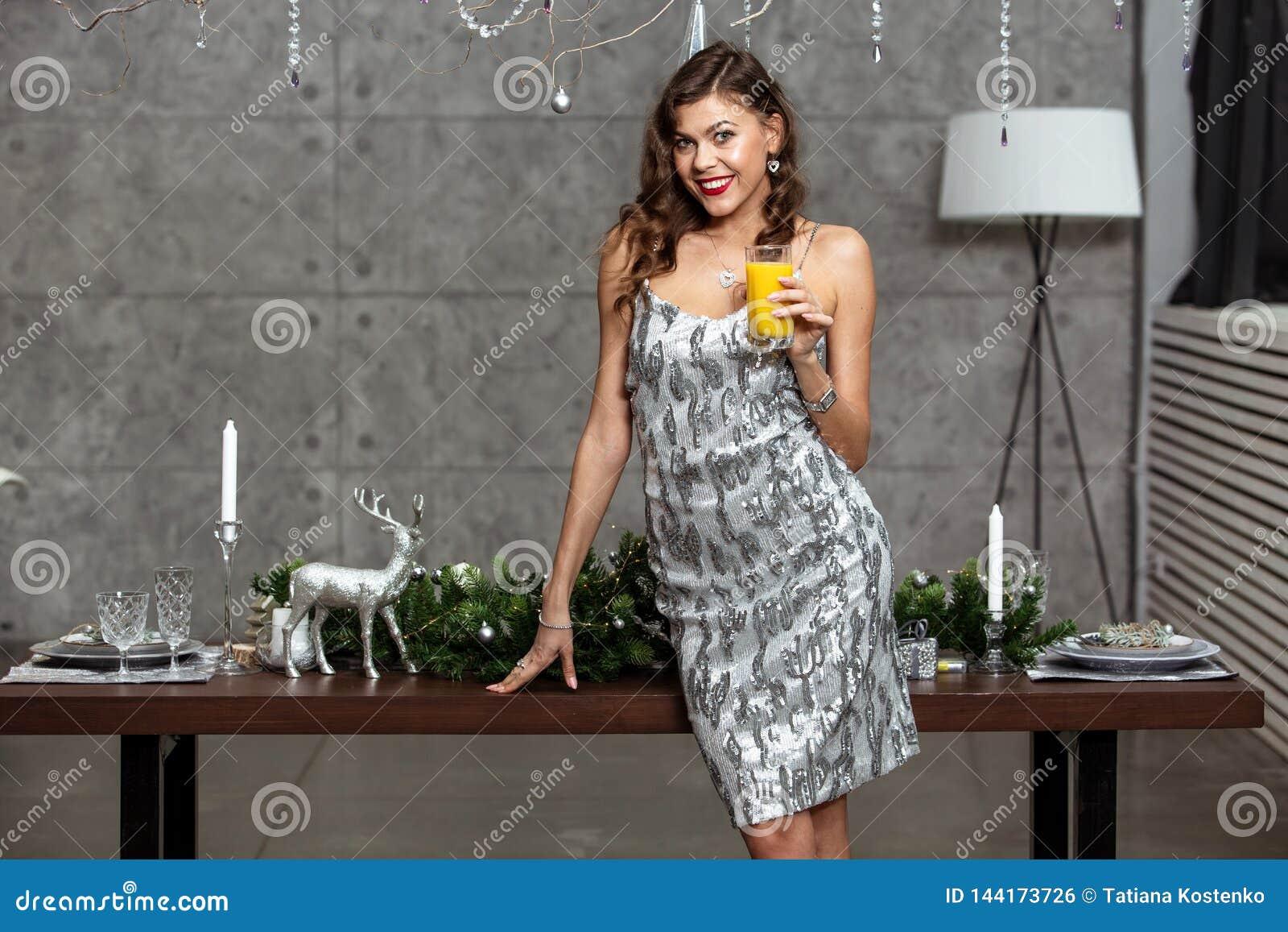Ładna brunetki dziewczyna trzyma szkło sok w olśniewającej szarej wieczór sukni stoi obok stołu z Nowym