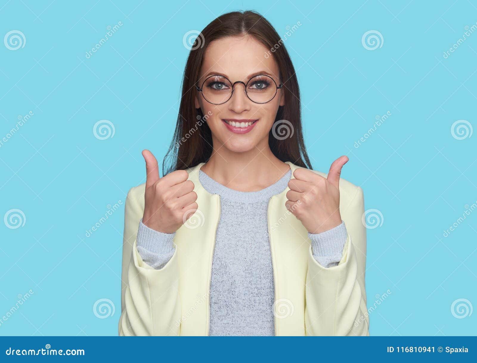Ładna dziewczyna ono uśmiecha się na kamerze z kciukiem up