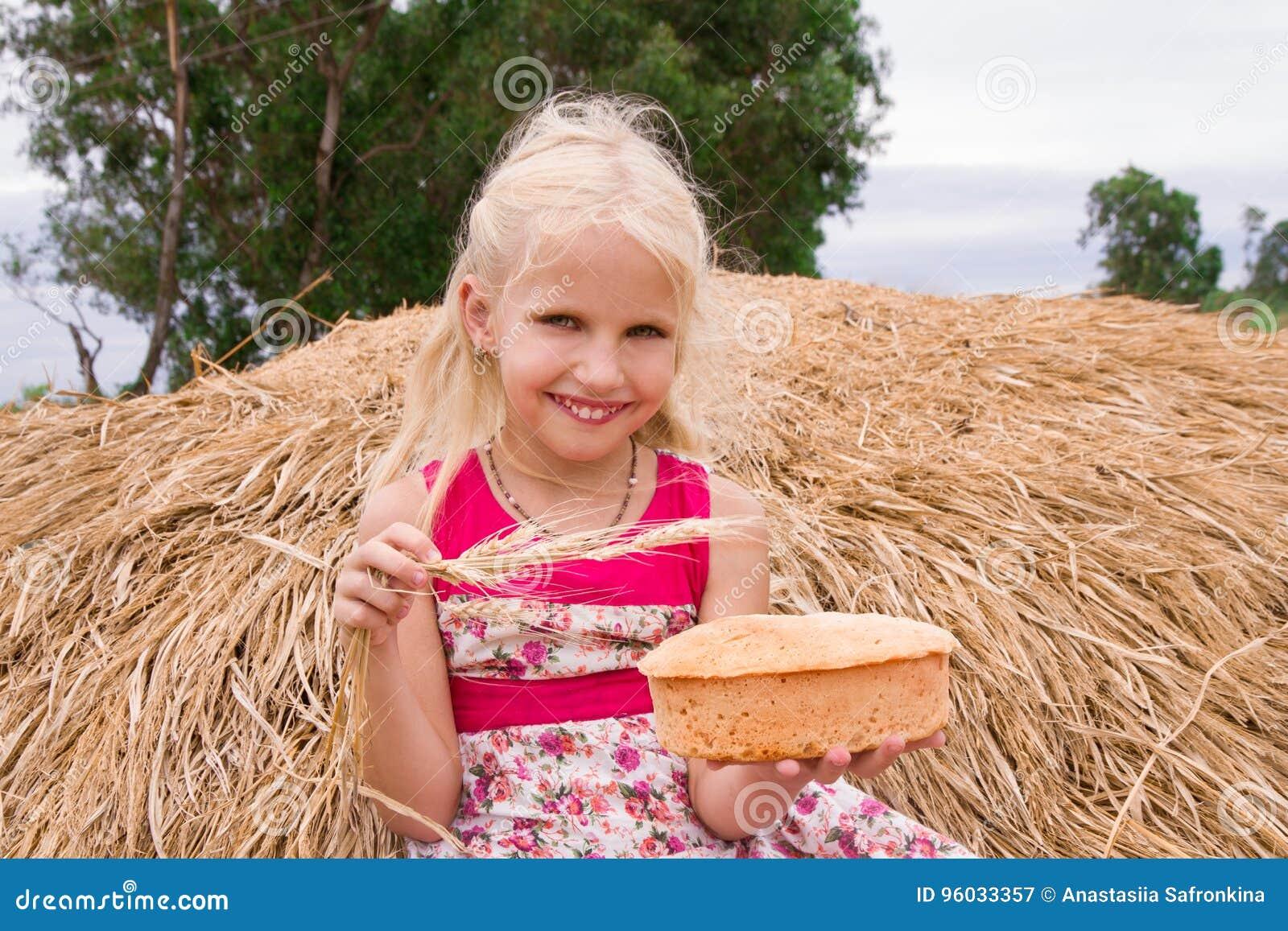 Ładna dziewczyna z chlebowym obsiadaniem na haystack