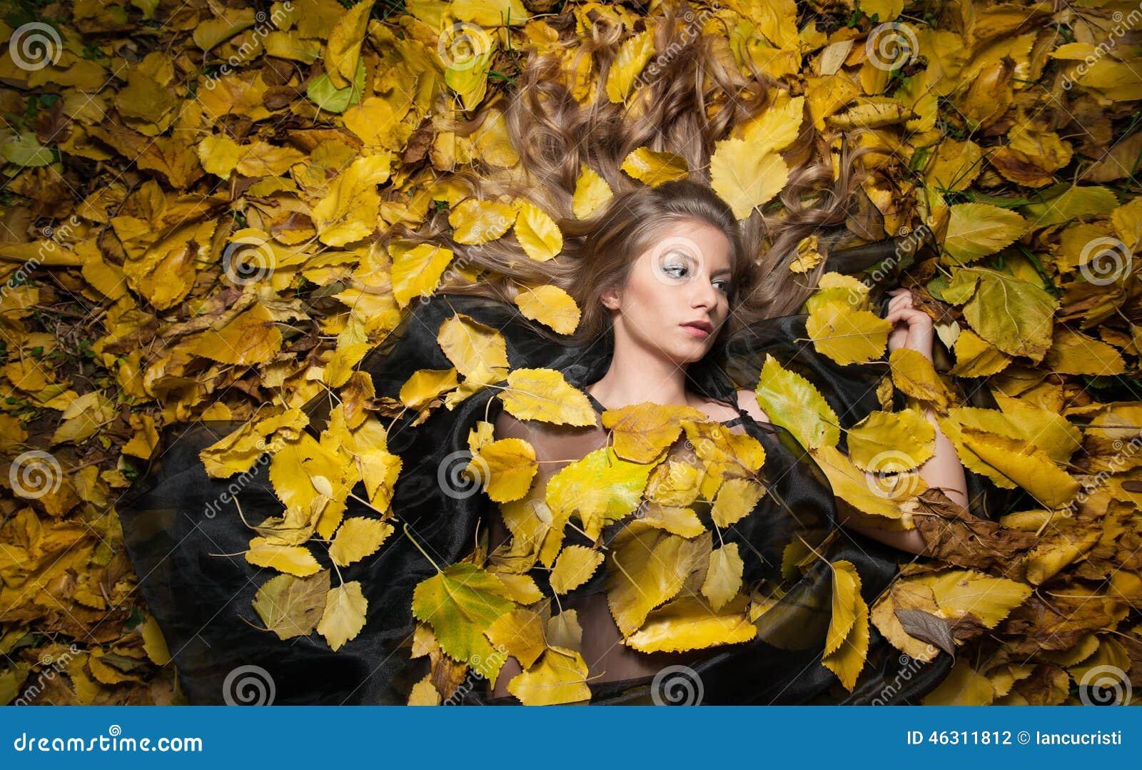 Ładna dziewczyna zakrywająca z jesiennymi liśćmi Młoda kobieta kłaść w dół na ziemi zakrywającej spadku ulistnieniem w parku seks