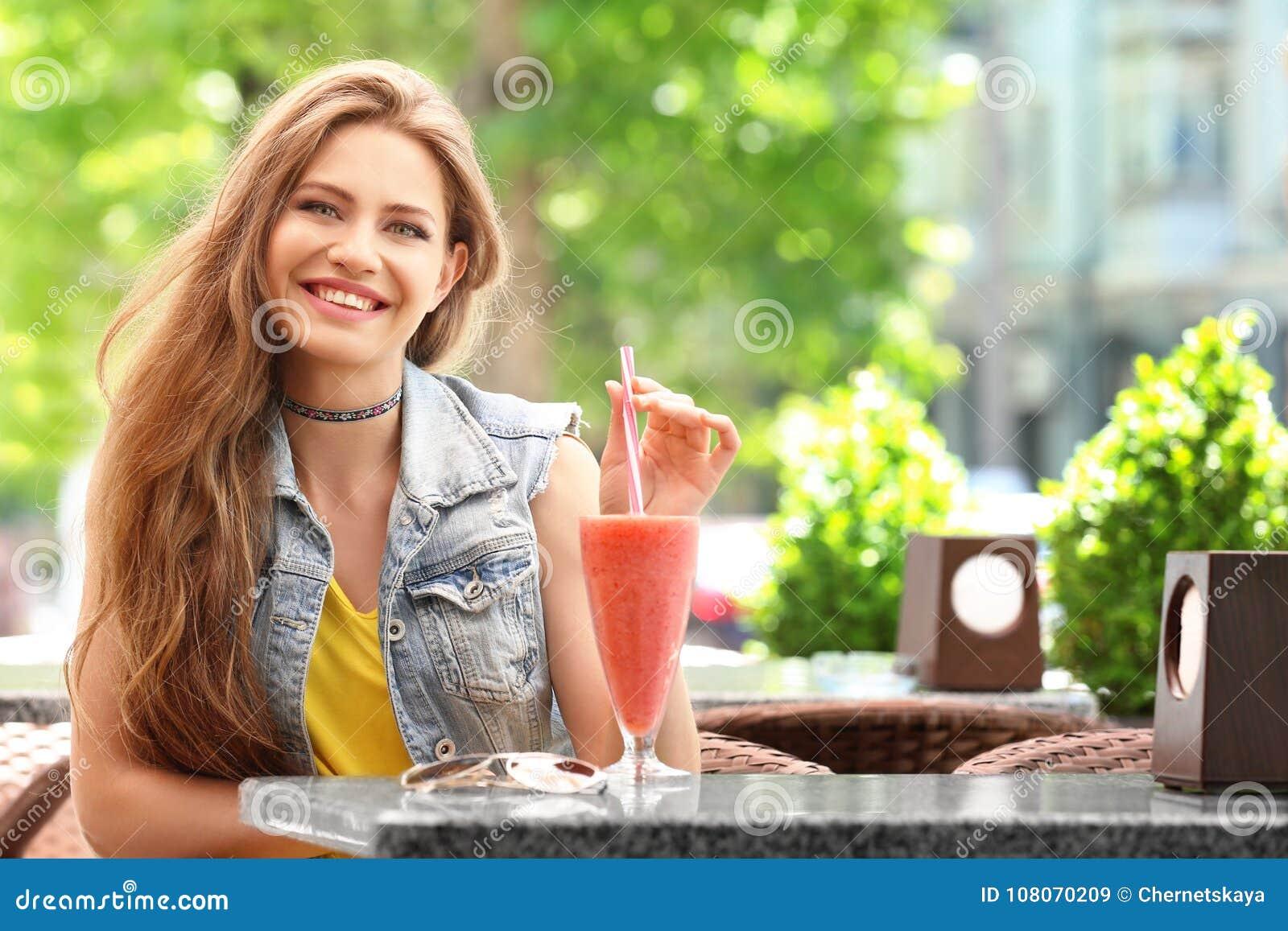 Ładna kobieta pije smakowitego smoothie