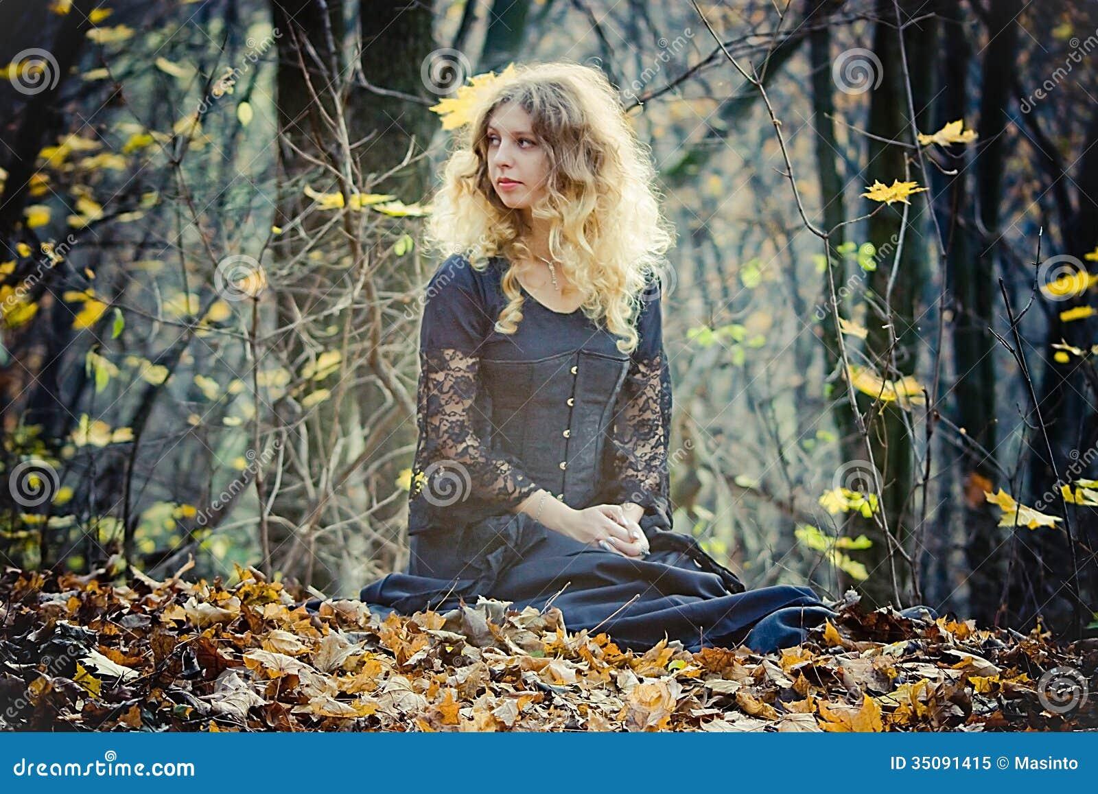 Ładna kobieta siedzi w czarodziejskim drewnie