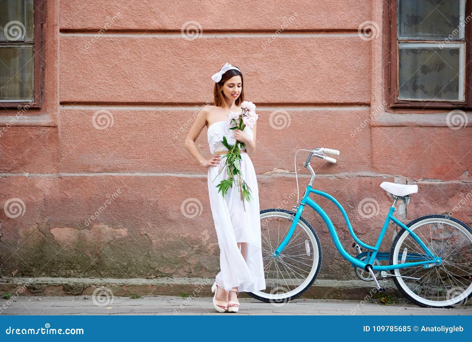 Ładna kobieta w bielu smokingowy pozować z kwiatami i błękitnym rowerem przed starą czerwieni ścianą