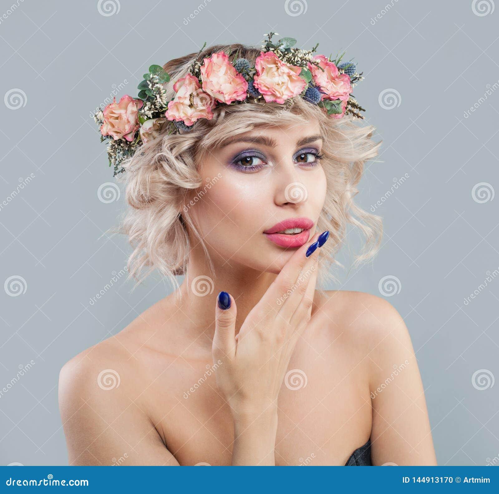 Ładna kobieta z jasną skórą, makeup, kwiatami i skrótu ostrzyżenia kędzierzawym portretem,