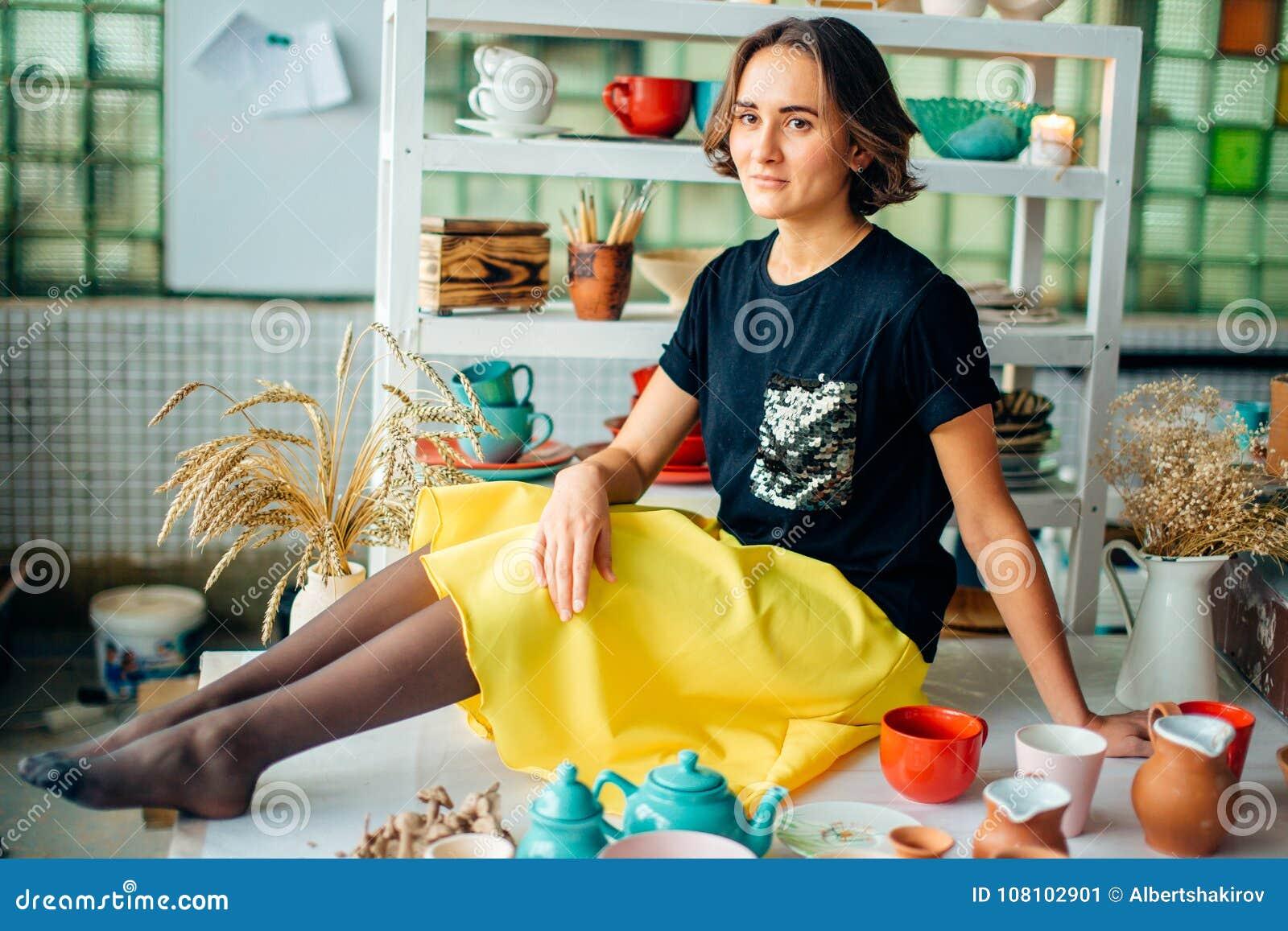 Ładna kobiety garncarka z glinianą filiżanką