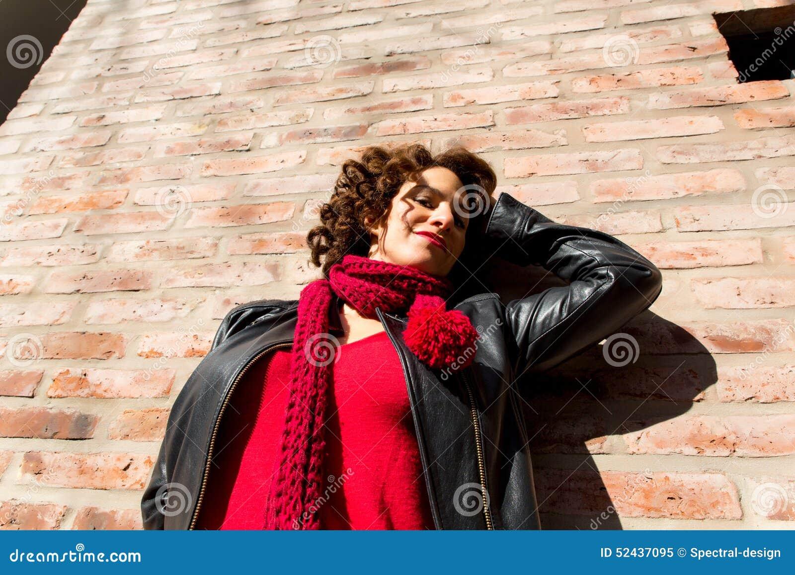 Ładna kobiety pozycja przy ściana z cegieł