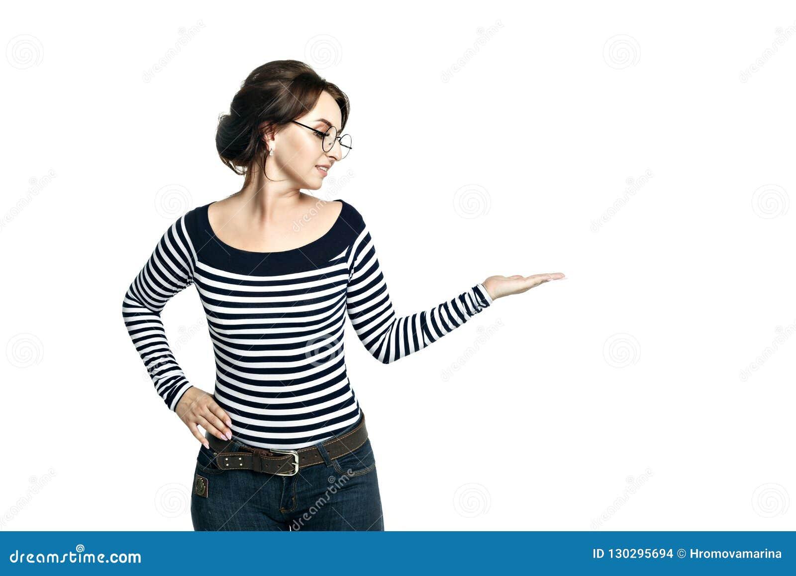 Ładna młoda kobieta w pasiastych ciasnych bluzki i round szkłach pokazuje wskazywać ręka gest, odosobnionego na białym tle
