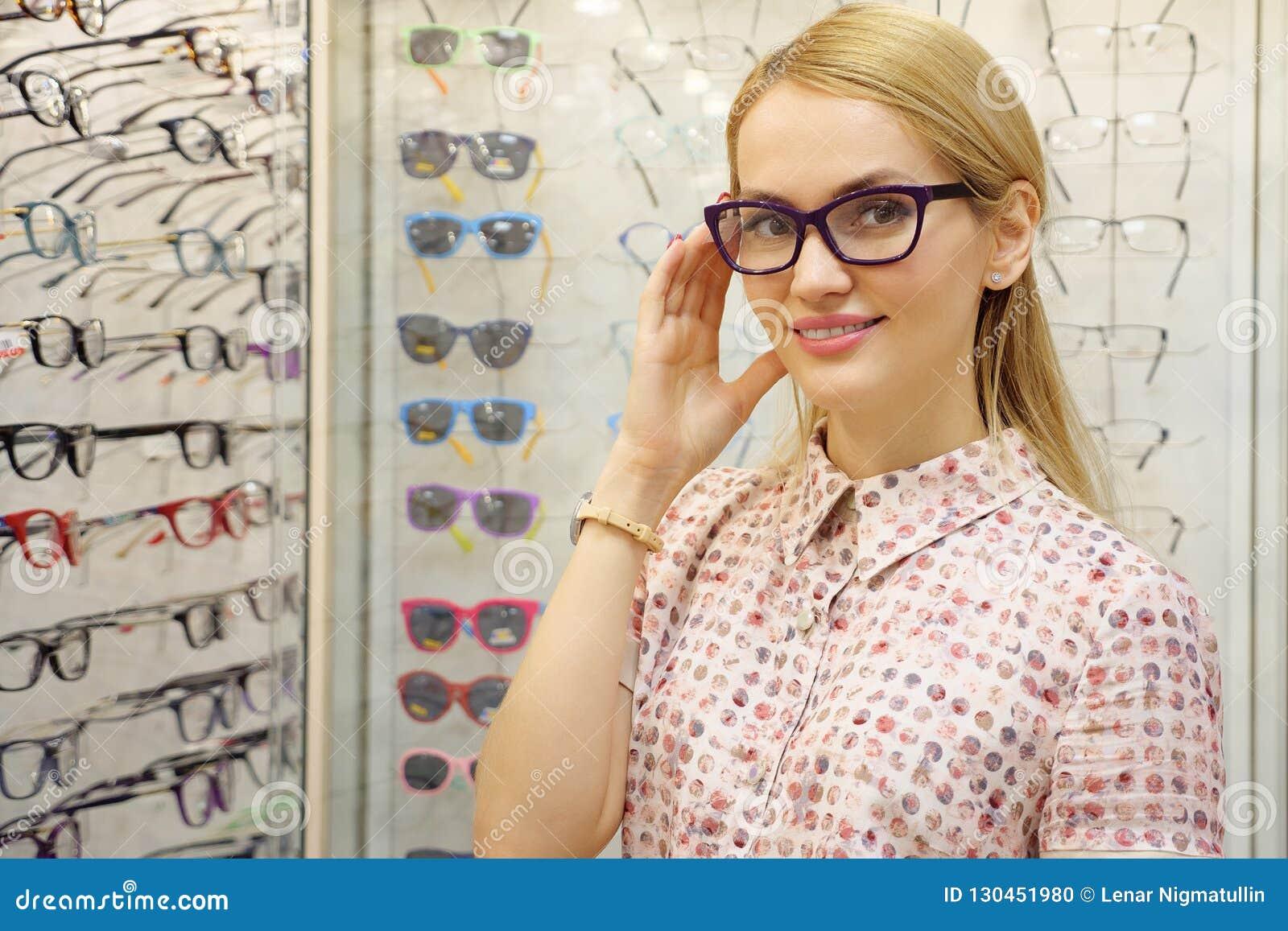 Ładna młoda kobieta wybiera szkła w okulisty sklepie