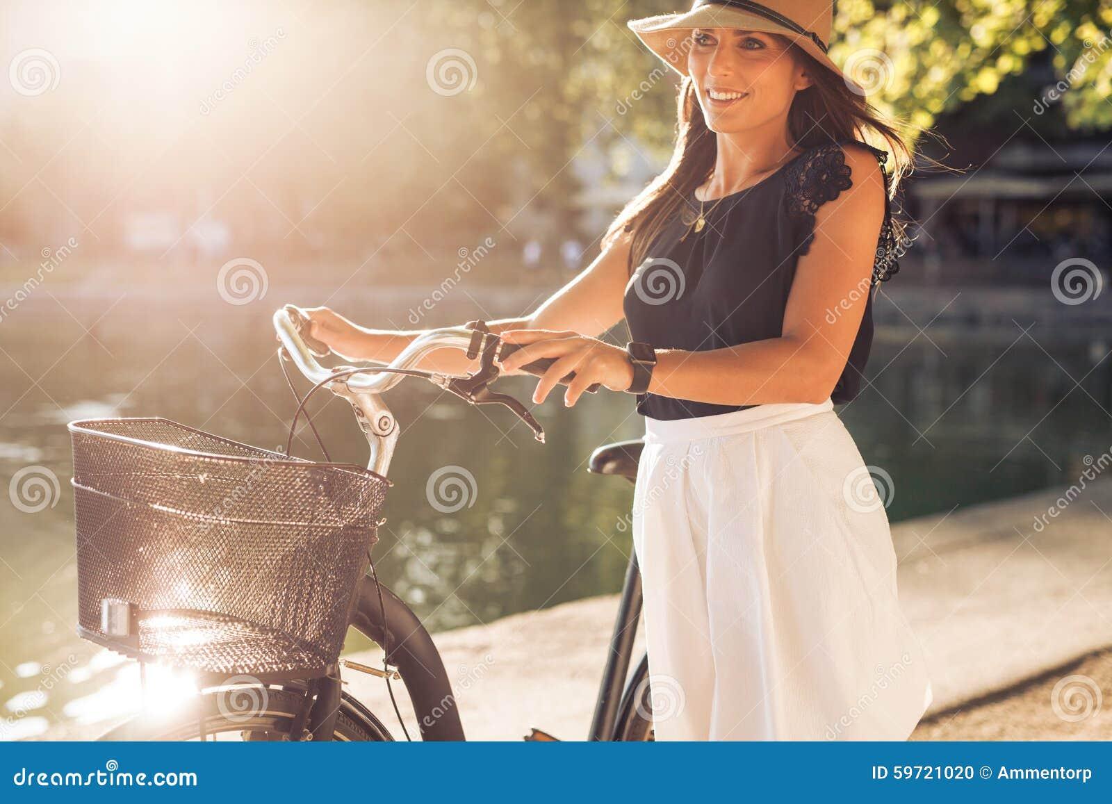 Ładna młoda kobieta z bicyklem w parku