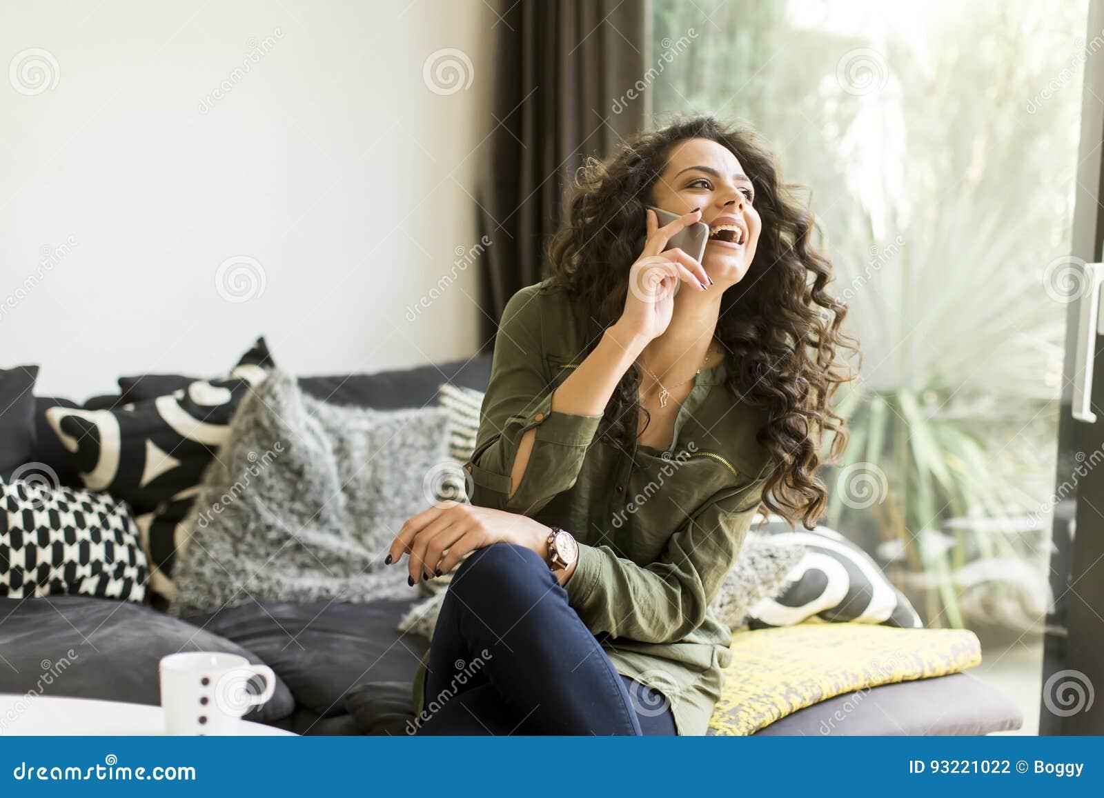 Ładna młoda kobieta z telefonem komórkowym w pokoju