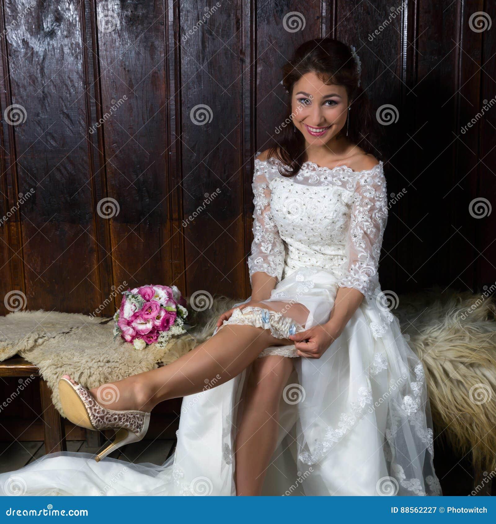 Ładna młoda panna młoda bawić się z jej podwiązką