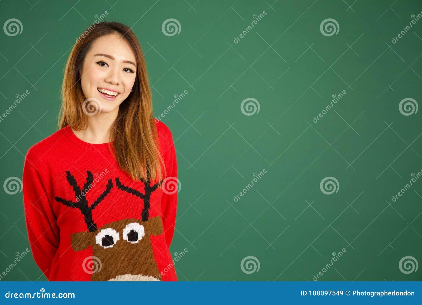 Ładna młoda singapurska dziewczyna jest ubranym Bożenarodzeniową bluzę i smili