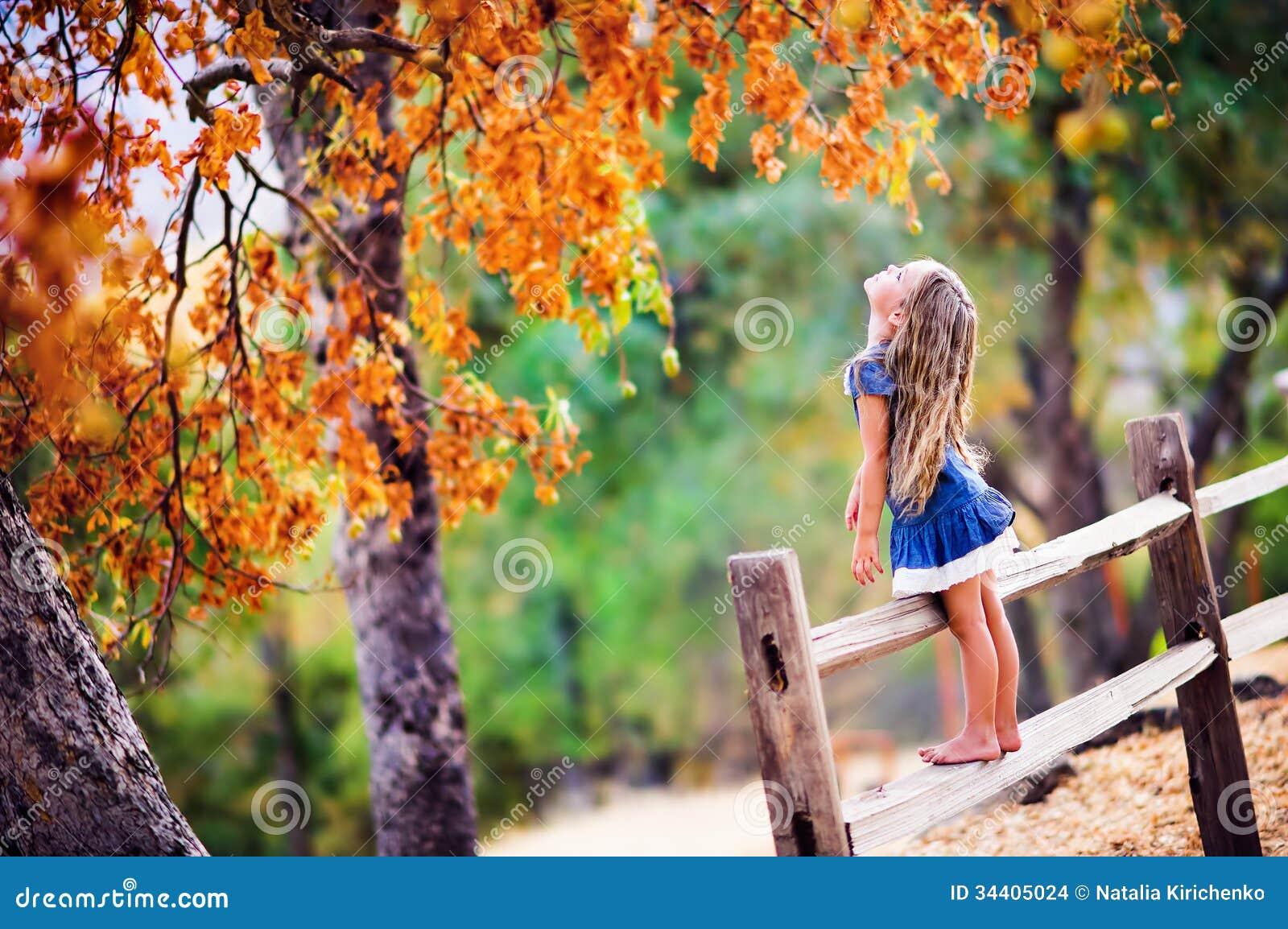 Ładna mała dziewczynka na piękno jesieni krajobrazu tle