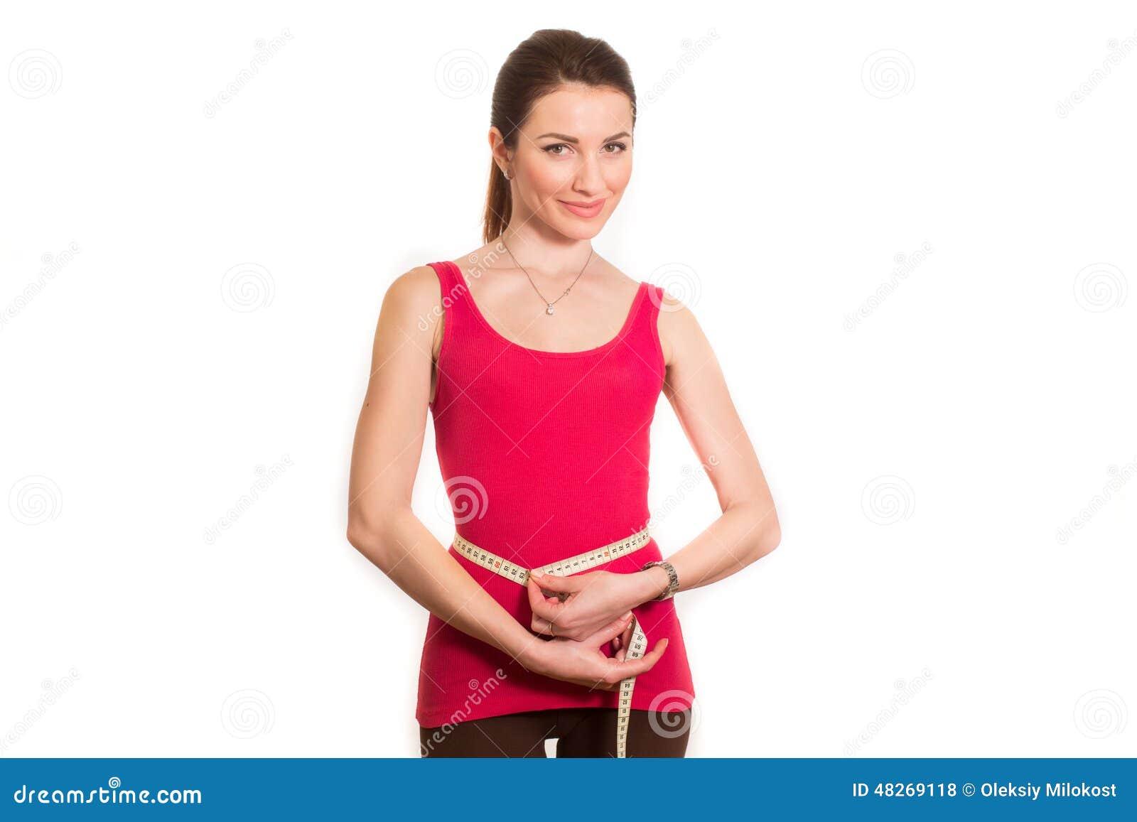 Ładna sprawności fizycznej dziewczyna mierzy jej talię odizolowywającą
