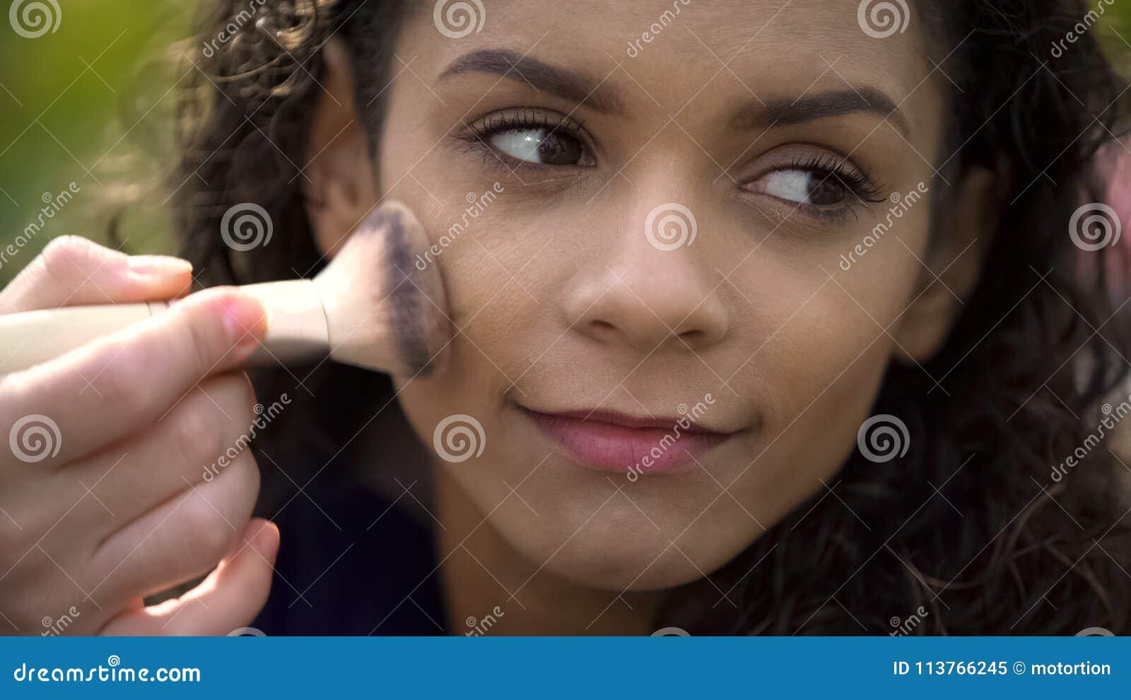 Ładna twarz piękna uśmiechnięta żeńska aktorka, makijażu artysta stosuje proszek
