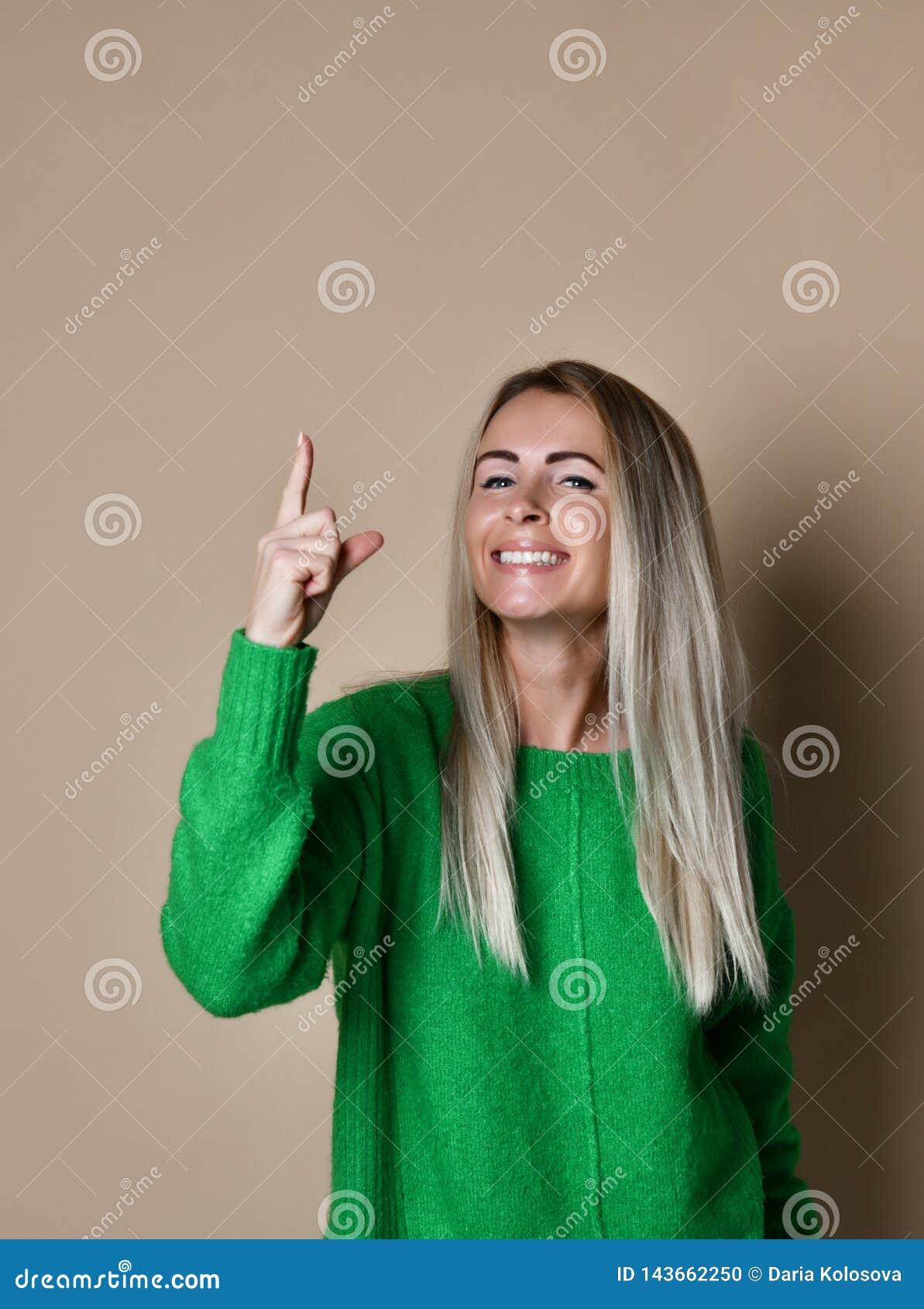 Ładna uśmiechnięta młoda blondynki dziewczyna wskazuje palec do na beżowym tle rysuje uwagę ważna informacja