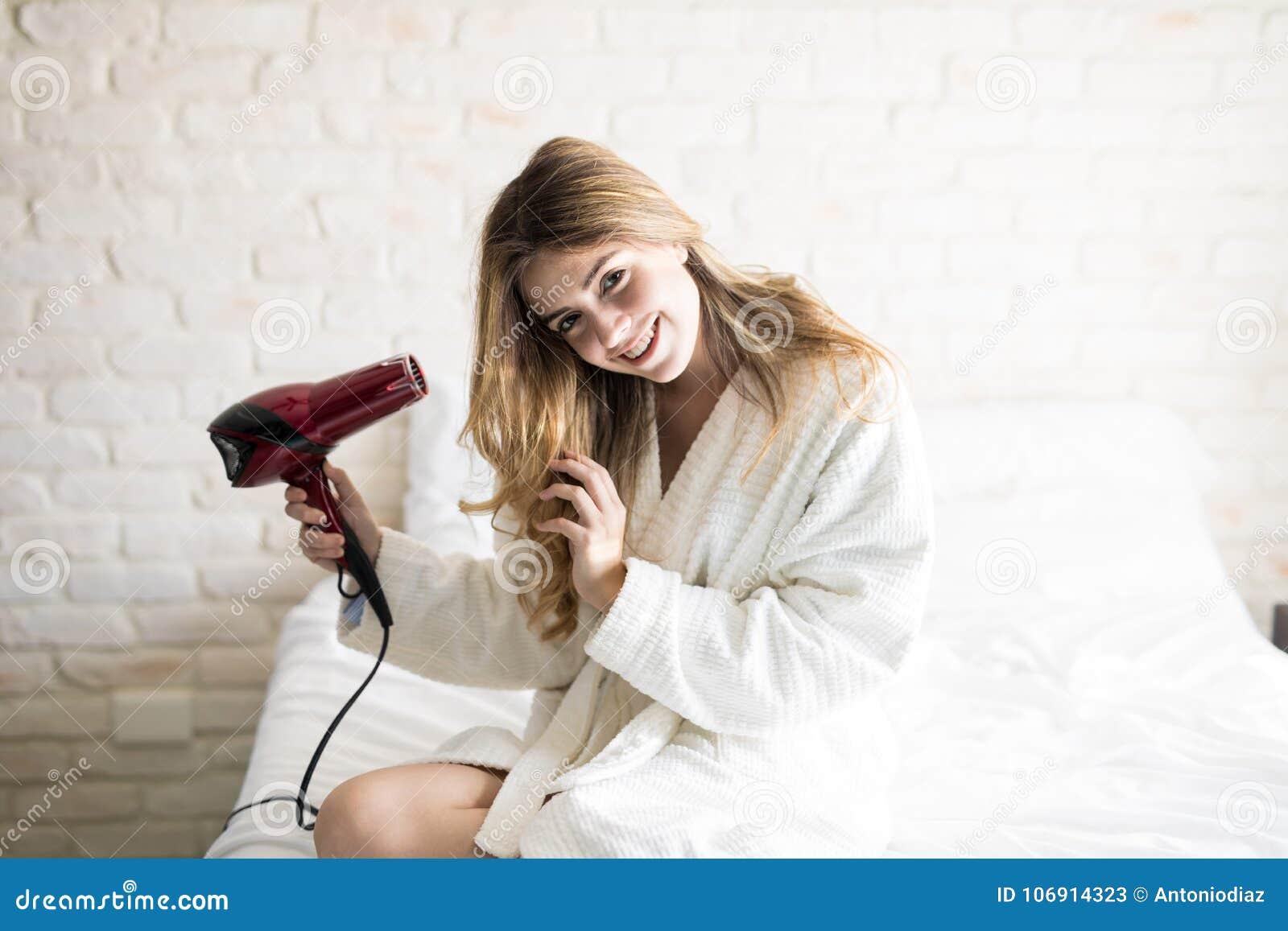 Ładny dziewczyna cios suszy jej włosy
